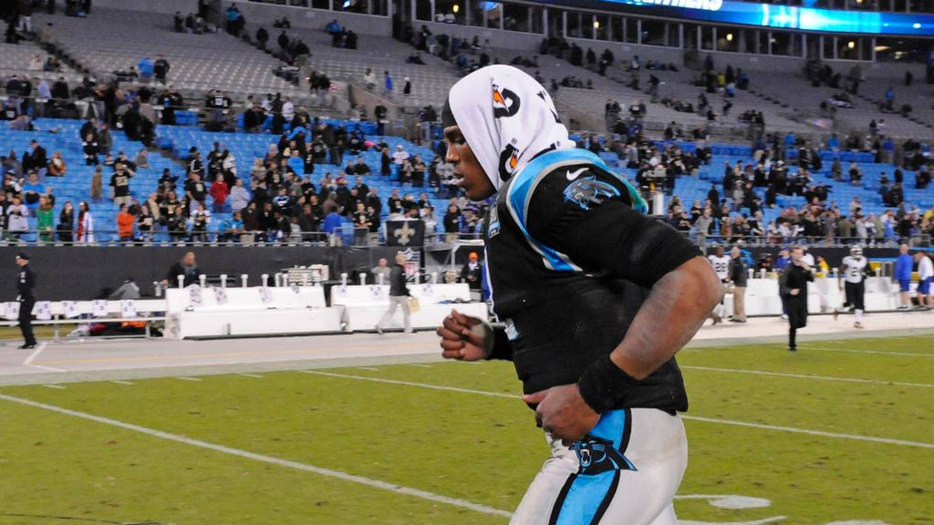 Carolina Panthers' Cam Newton (1) runs off the field after an NFL football game against the New Orleans Saints in Charlotte, N.C., Thursday, Oct. 30, 2014. The Saints won 28-10. (AP Photo/Mike McCarn)