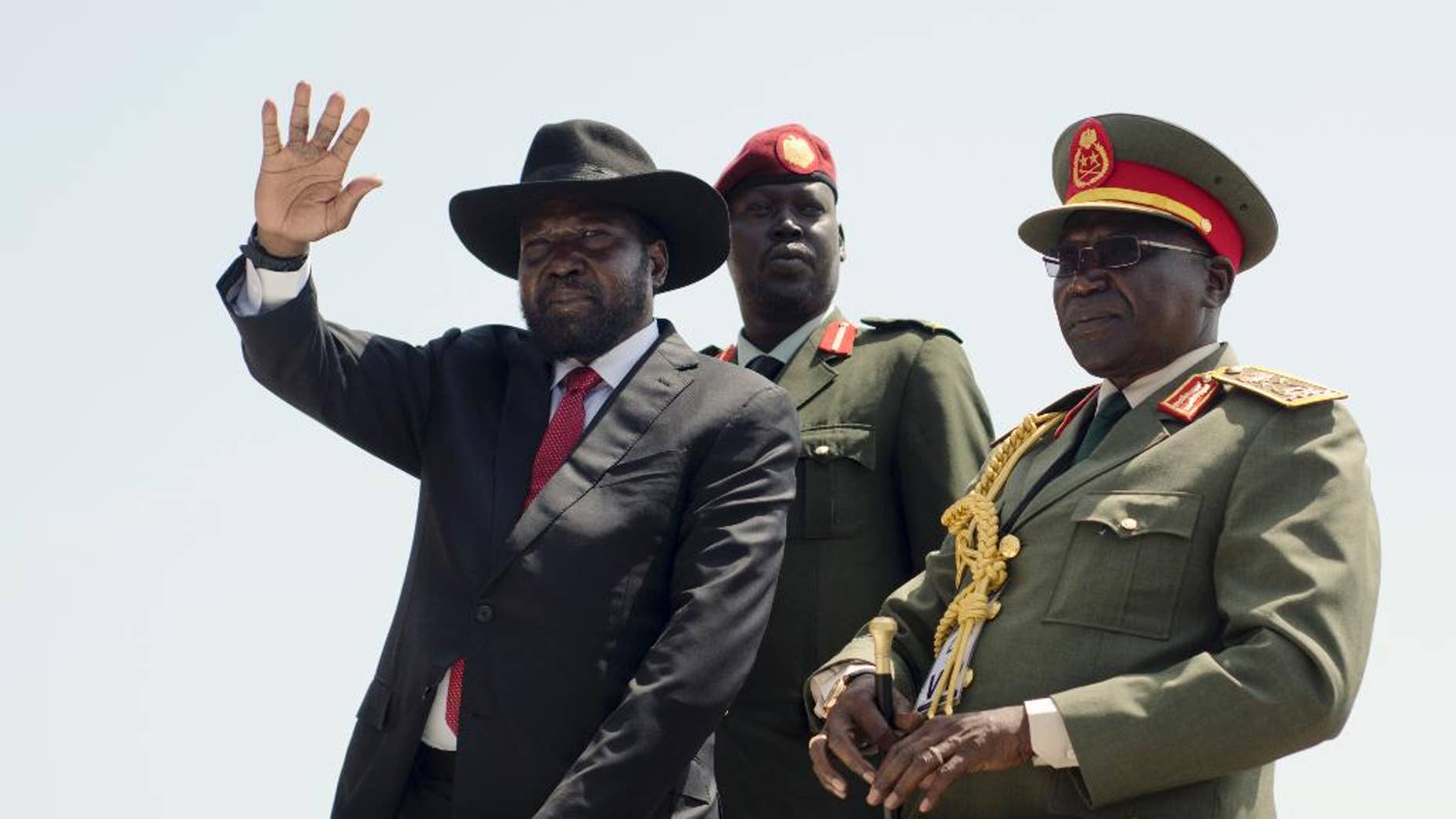 FILE - In this Thursday, July 9, 2015 file photo, South Sudan's President Salva Kiir, left, accompanied by army chief of staff Paul Malong, right, waves during an independence day ceremony in the capital Juba, South Sudan. A spokesman said Wednesday, Feb. 8, 2017 that Kiir will seek election next year, in what will be the first vote on Salva Kiir's leadership since the turbulent country won independence. (AP Photo/Jason Patinkin, File)