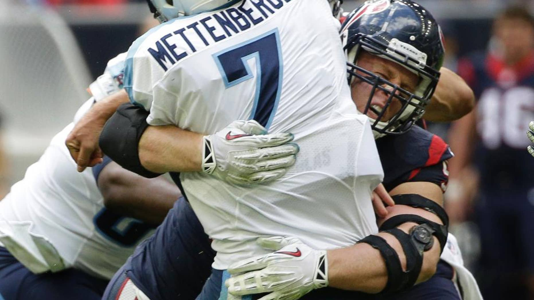 Houston Texans defensive end J.J. Watt tackles Tennessee Titans quarterback Zach Mettenberger (7) during the first half of an NFL football game Sunday, Nov. 30, 2014, in Houston. (AP Photo/David J. Phillip)