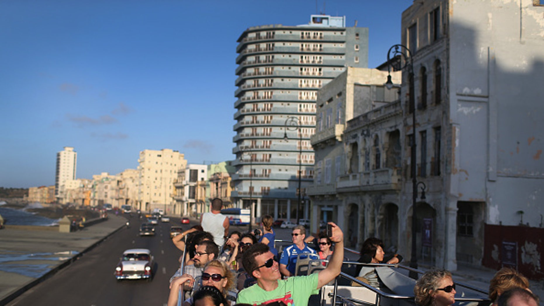 Tourists take in the sites from a double decker tour bus of Havana.