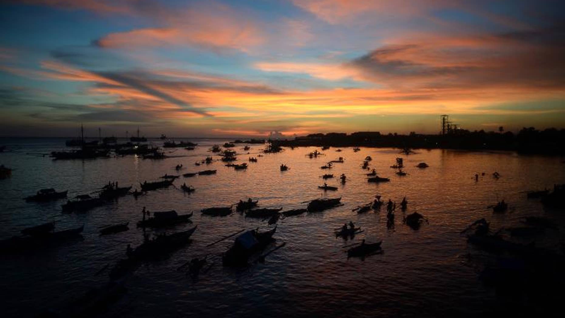 Evacuees affected by the stand-off between Philippine government forces and Muslim rebels sit anchored in their wooden boats used also as temporary living quarters at sunset near the sea wall in Zamboanga on September 14, 2013.