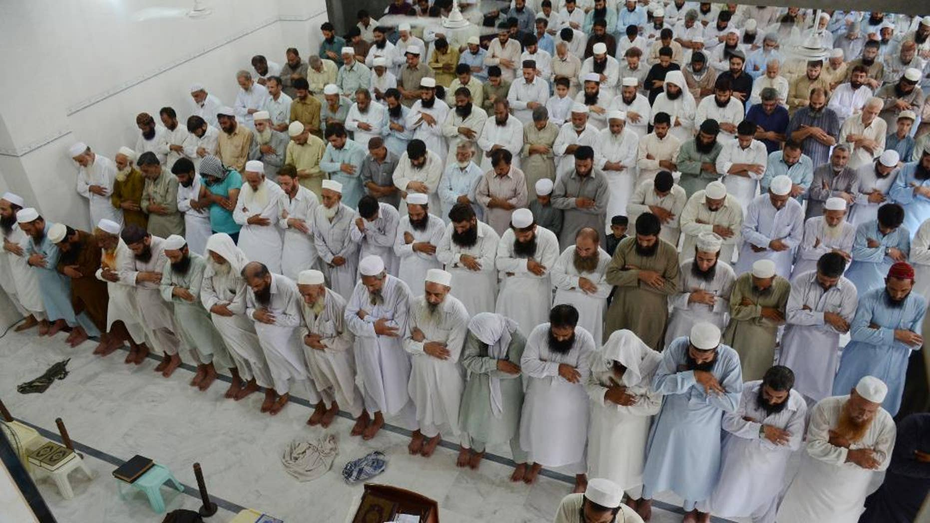 People offer funeral prayers for Taliban leader Mullah Mohammad Omar at a mosque in Peshawar, Pakistan, Friday, July 31, 2015. Afghanistan's Taliban on Thursday confirmed the death of Mullah Omar, who led the group's self-styled Islamic emirate in the 1990s, sheltered al-Qaida through the 9/11 attacks and led a 14-year insurgency against U.S. and NATO troops. (AP Photo/Mohammad Sajjad)