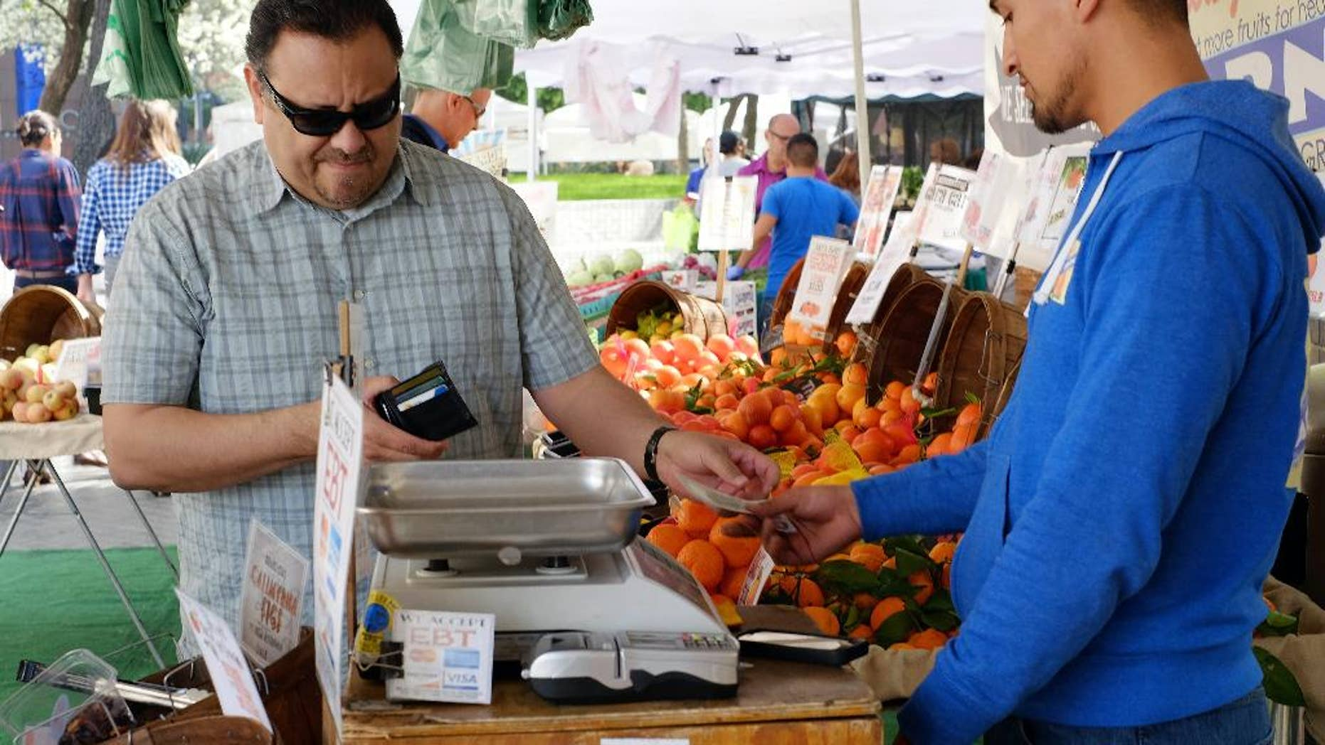 FILE - In this Friday, Feb. 6, 2015 file photo, a shopper pays for his produce at a farmers market in downtown Los Angeles.  The Commerce Department releases its April report on consumer spending, which accounts for 70 percent of economic activity, on Monday, June 1, 2015. (AP Photo/Richard Vogel, File)