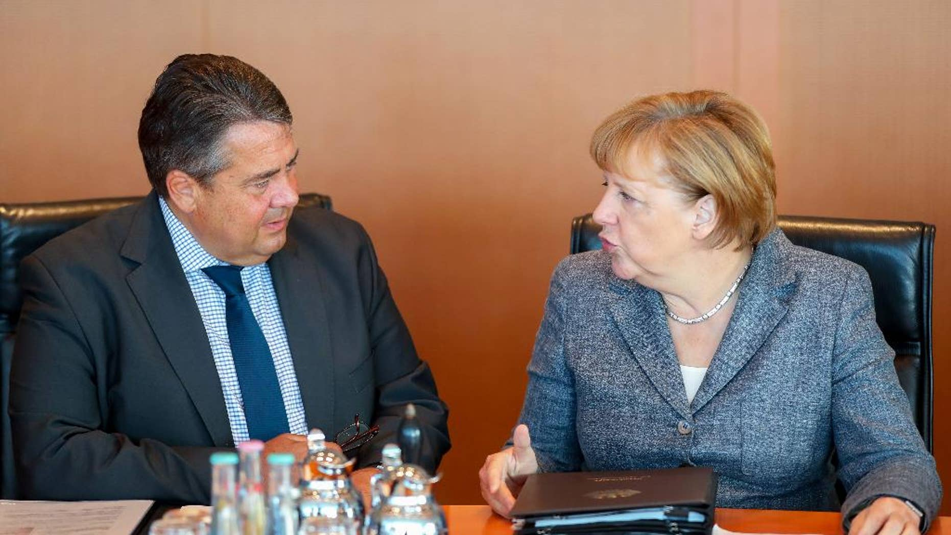 German Chancellor Angela Merkel, right,  and German Economics Minister Sigmar Gabriel attend  a cabinet meeting at the chancellery  in Berlin, Germany,  Wednesday  Aug. 17,  2016.  (Kay Nietfeld/dpa via AP)