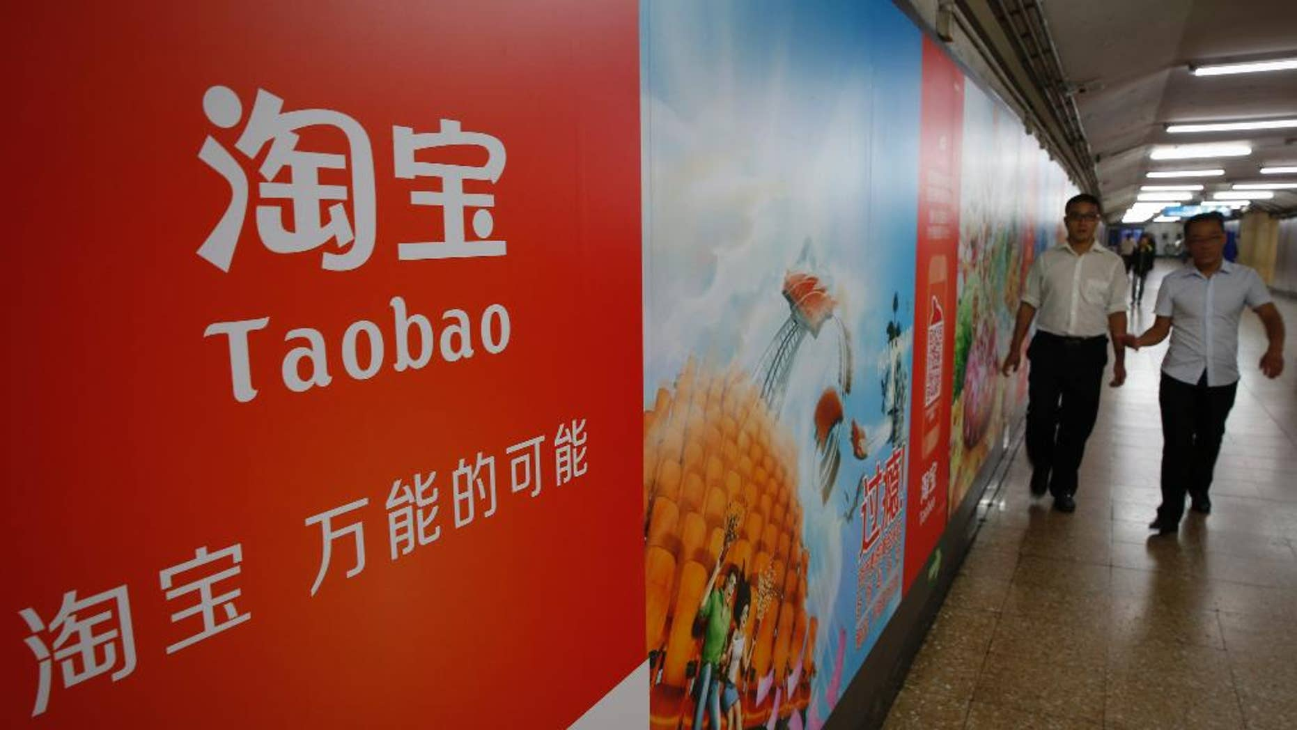 FILE - In this Sept. 18, 2014 file photo, people walk past an advertising billboard showing the mobile app of Alibaba's Taobao consumer-to-consumer site at a subway station in Beijing. Alibaba Group Holding Ltd. reports quarterly financial results before the market opens on Wednesday, Aug. 12, 2015. (AP Photo/Vincent Thian, File)