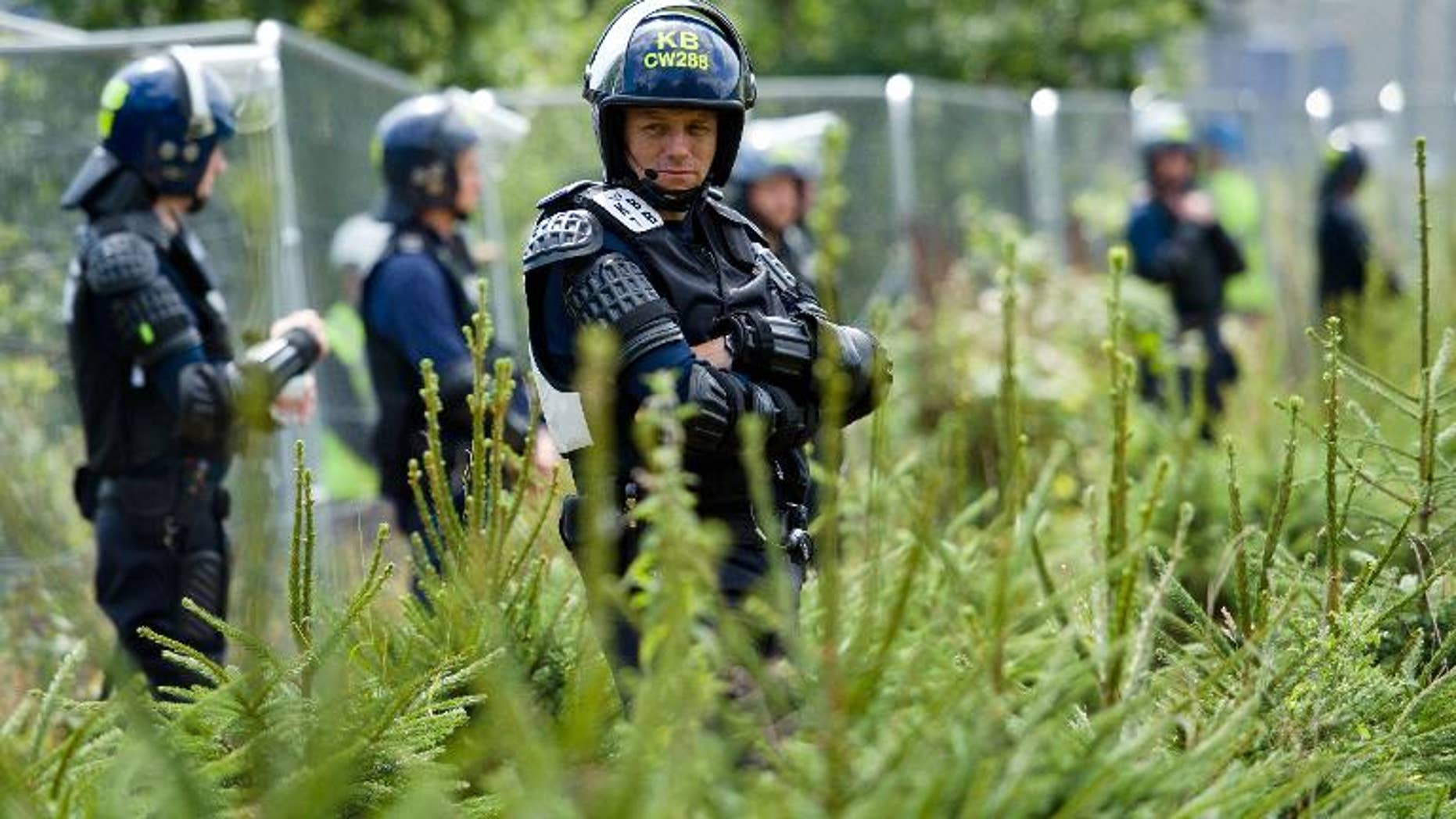 Police officers in body armour line the perimeter fence of the test drill site operated by British energy firm Cuadrilla Resources in Balcombe, southern England, on August 20, 2013, as anti-fracking activists hold a protest camp nearby.