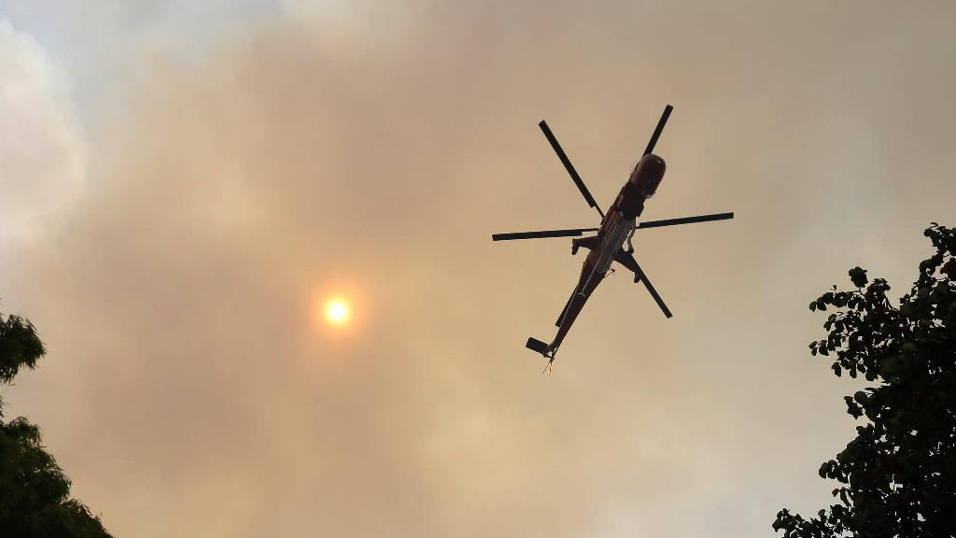 An helicopter flies over a forest at the village of Limni on the island of Evia, about 160 kilometers (100 miles) north of Athens, Monday, Aug. 1, 2016. Nearly 200 firemen, assisted by water-dropping aircraft, fire engines and volunteers, are fighting a large forest fire that has raged through the Greek island of Evia for the past three days. (AP Photo/Thanassis Stavrakis)