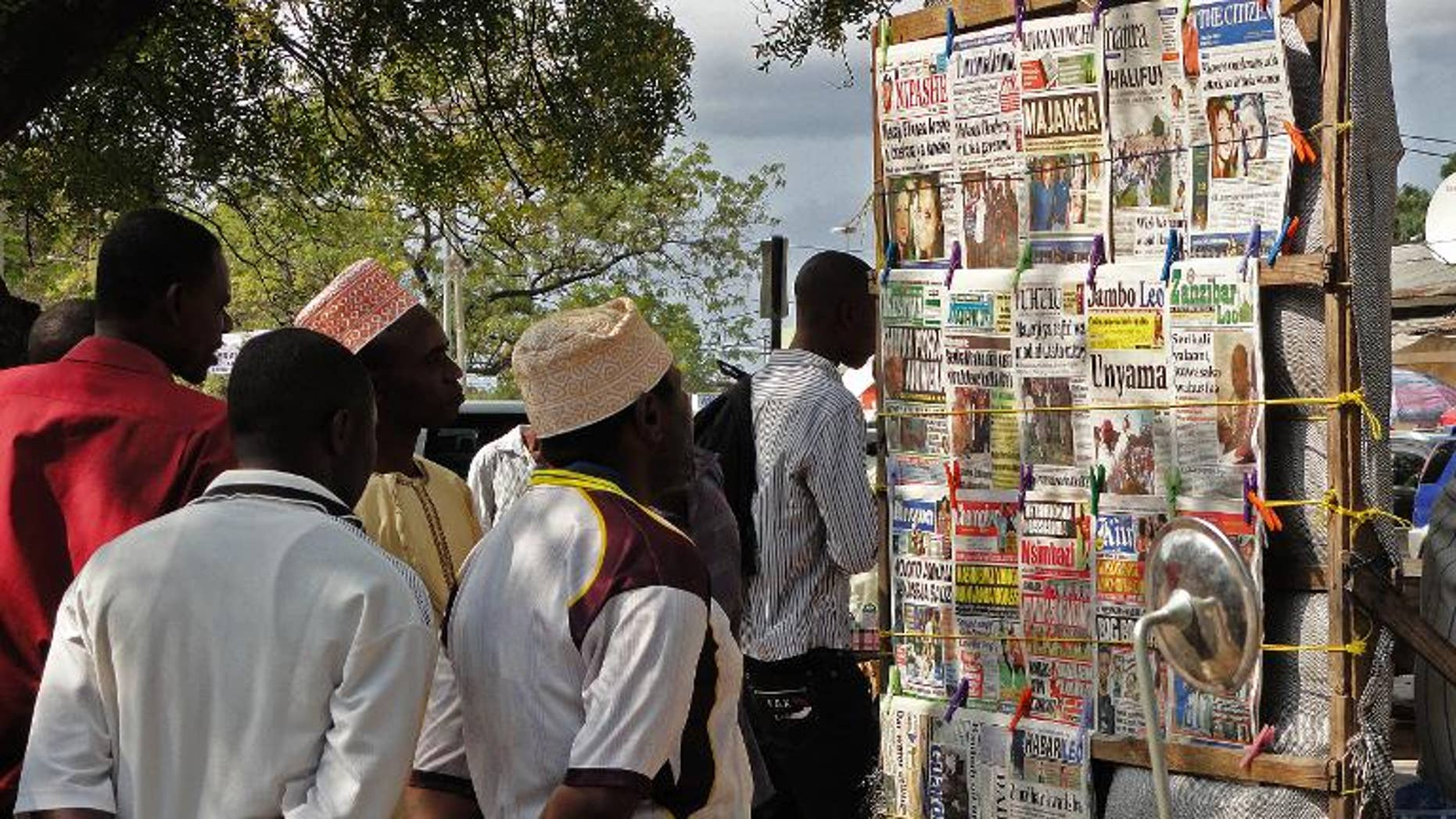 Locals look at newspaper headlines in Stone Town on the Indian Ocean island of Zanzibar on August 9, 2013
