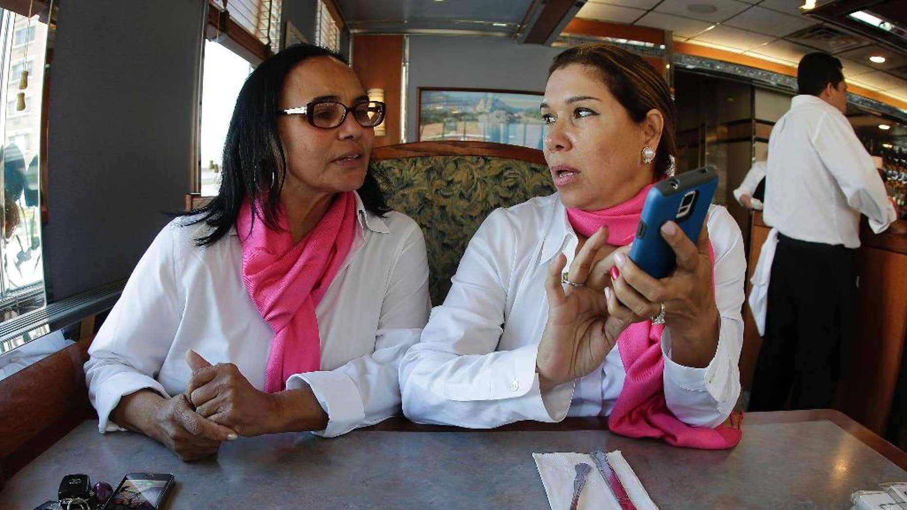 Dinorah De Cruz, left, talks with Stella Mateo, founder of the SheTaxi/SheRides car service, while taking a lunch break, Monday, Sept. 15, 2014, in New York.