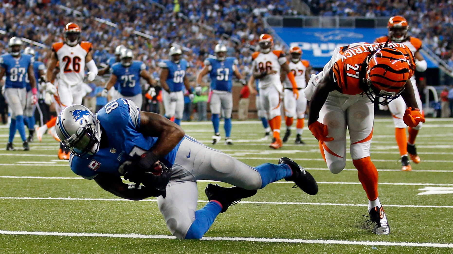 Detroit Lions wide receiver Calvin Johnson (81) catches a 27-yard touchdown reception as Cincinnati Bengals cornerback Dre Kirkpatrick (27) defends in the second half of an NFL football game on Sunday, Oct. 20, 2013, in Detroit. (AP Photo/Rick Osentoski)