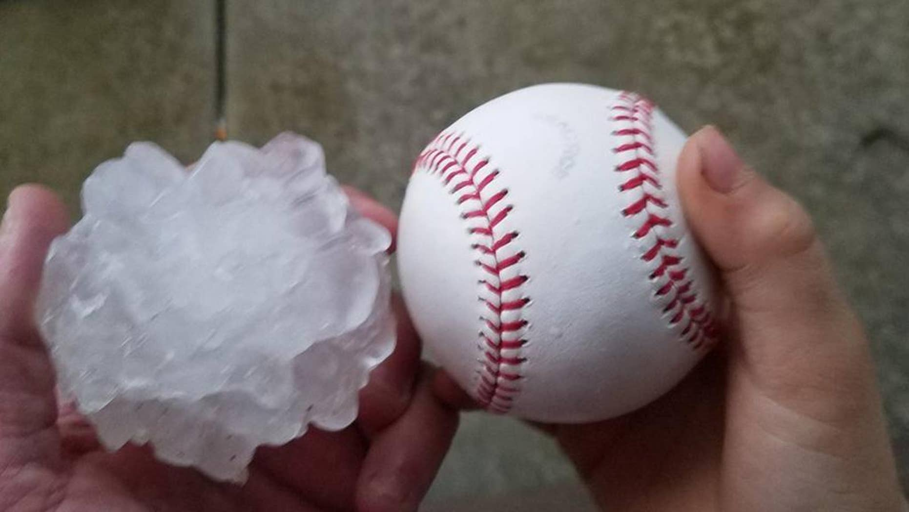 This photo provided by Tim Creedon shows his baseball and a hailstone that fell in the backyard of Creedon's home in Ottawa, Ill., Tuesday, Feb. 28, 2017. Illinois Gov. Bruce Rauner has activated the state's emergency operations center as local officials reported damage from tornados spawned by a late-winter storm system. (Tim Creedon via AP)
