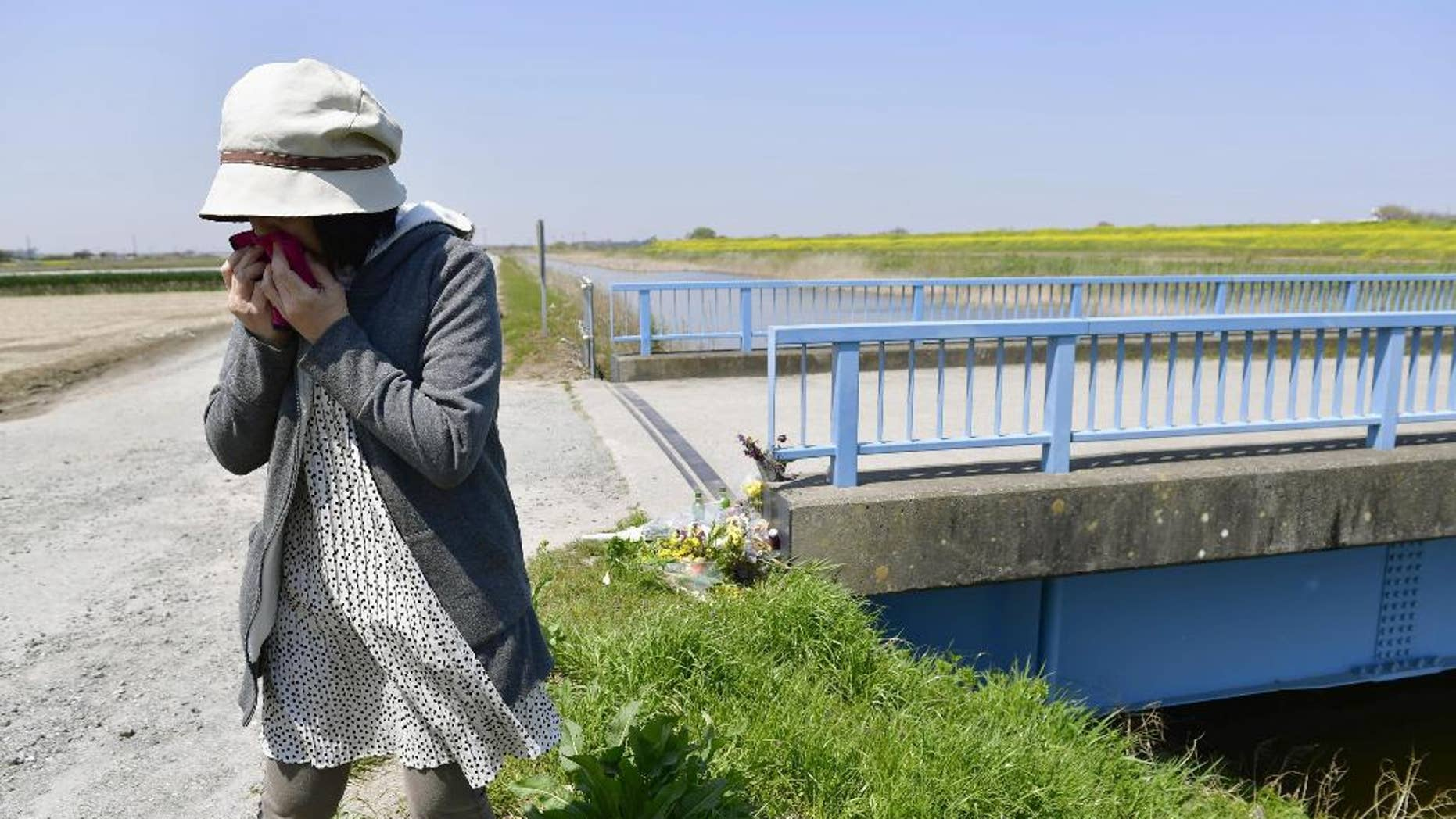 A woman sobs after offering flowers where a 9-year-old Vietnamese girl was found dead in Abiko, near Tokyo, Friday, April 14, 2017. Police have arrested a Japanese man in connection with the girl's death, weeks after her naked body was found near a trench. Chiba prefectural police said Friday they arrested 46-year-old real estate salesman Yasumasa Shibuya on suspicion he abandoned the girl's body. Japanese media say Shibuya headed a parents' association at the school the girl attended. (Ren Onuma/Kyodo News via AP)