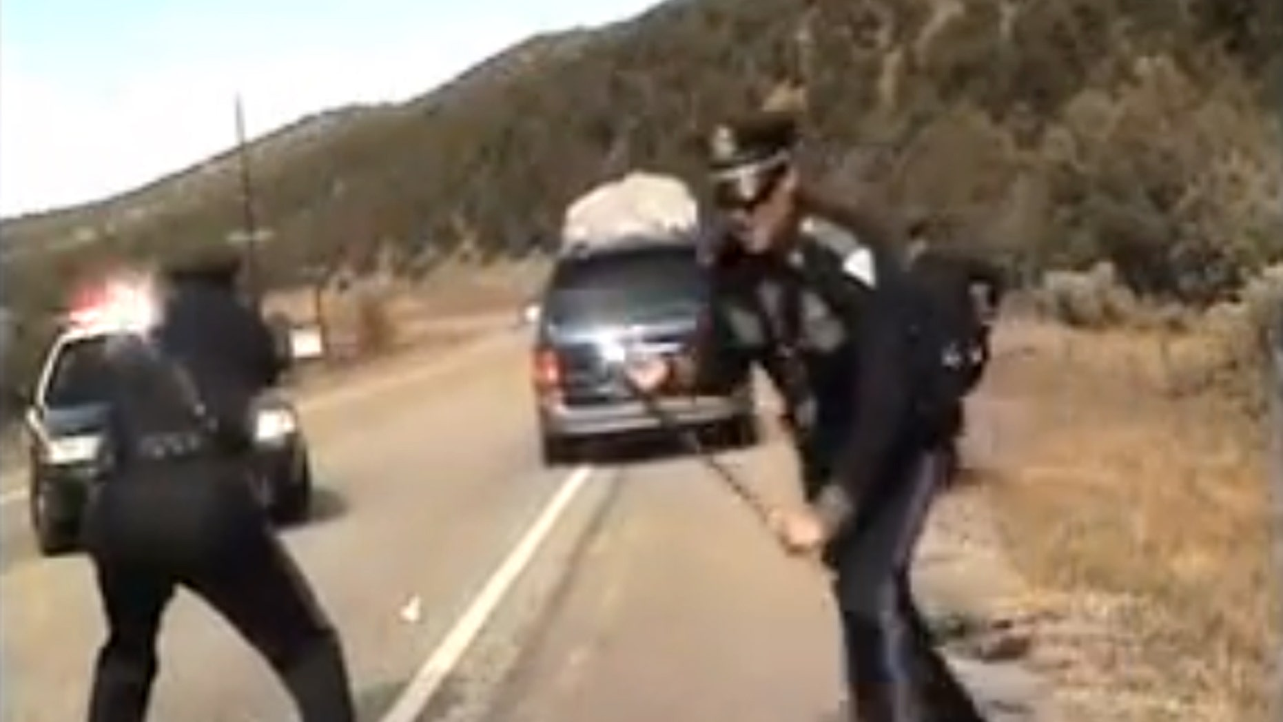 Three New Mexico State Police officers react as a minivan driven by motorist Oriana Farrell pulls away from a chaotic traffic stop that included one officer bashing the van's window with his night stick and another, Elias Montoya, at left, firing three shots as the van drives off, in this video made Oct. 28, from the dashboard camera of the police cruiser. Montoya, the officer who fired at the van full of children, has been suspended. (AP Photo/New Mexico State Police)