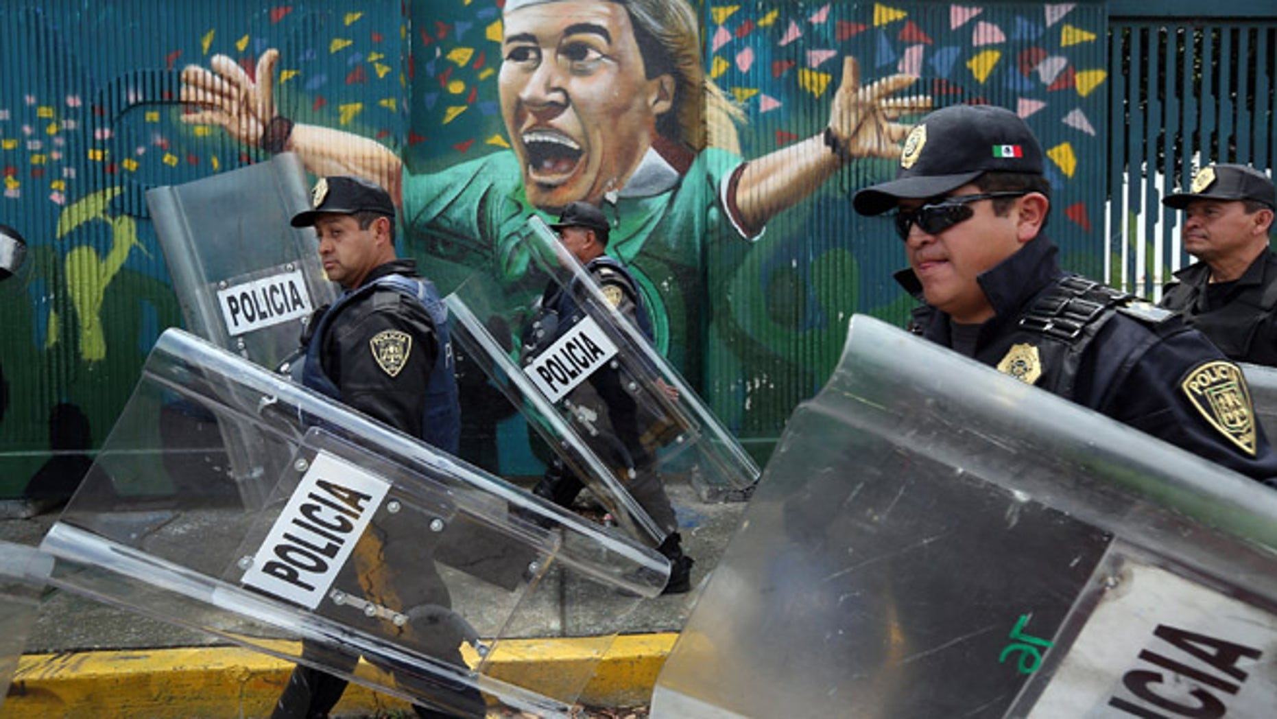 MEXICO CITY, MEXICO - JUNE 24: Police walk past a mural of Mexican soccer legend Luis Hernandez at the Azteca soccer stadium following the final campaign rally of Enrique Pena Nieto, presidential candidate for the Institutional Revolutionary Party (PRI), on June 24, 2012 in Mexico City, Mexico. Pena Nieto leads the polls going into the July 1 presidential election. If he wins, the PRI will return to power twelve years after losing the presidency to the ruling National Action Party (PAN), in 2000. (Photo by John Moore/Getty Images)