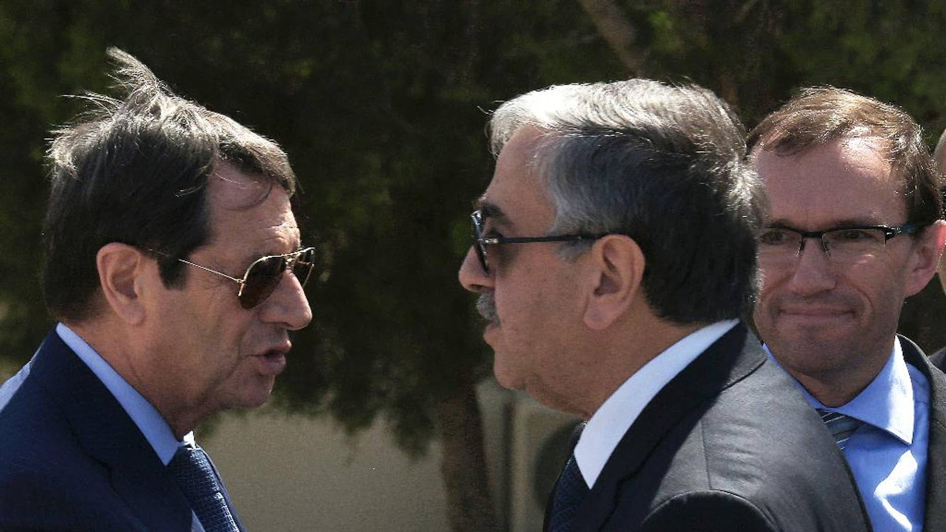 """FILE- In this Wednesday, Sept. 14, 2016 file photo, Cypriot President Nicos Anastasiades, left, and breakaway Turkish Cypriot leader Mustafa Akinci, right, talks as the UN Special Advisor of the Secretary-General Espen Barth Eide, right, looks on as they leave their talks aimed at reunifying the ethnically divided island, at the disused Nicosia airport inside a United Nations controlled buffer zone. Cyprus' president said Friday, Sept. 30, 2016, an insistence by breakaway Turkish Cypriots to cede Turkey the right to militarily intervene under a hoped-for deal reunifying the divided Mediterranean island nation is """"excessive and unjustified."""" (AP Photo/Petros Karadjias, File)"""
