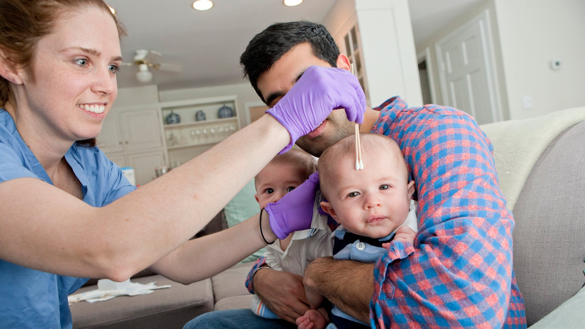 Jan. 29, 2016: This image shows NYU senior research coordinator Nora Henderson collecting samples of bacteria from twin boys at their Mamaroneck, N.Y., home.