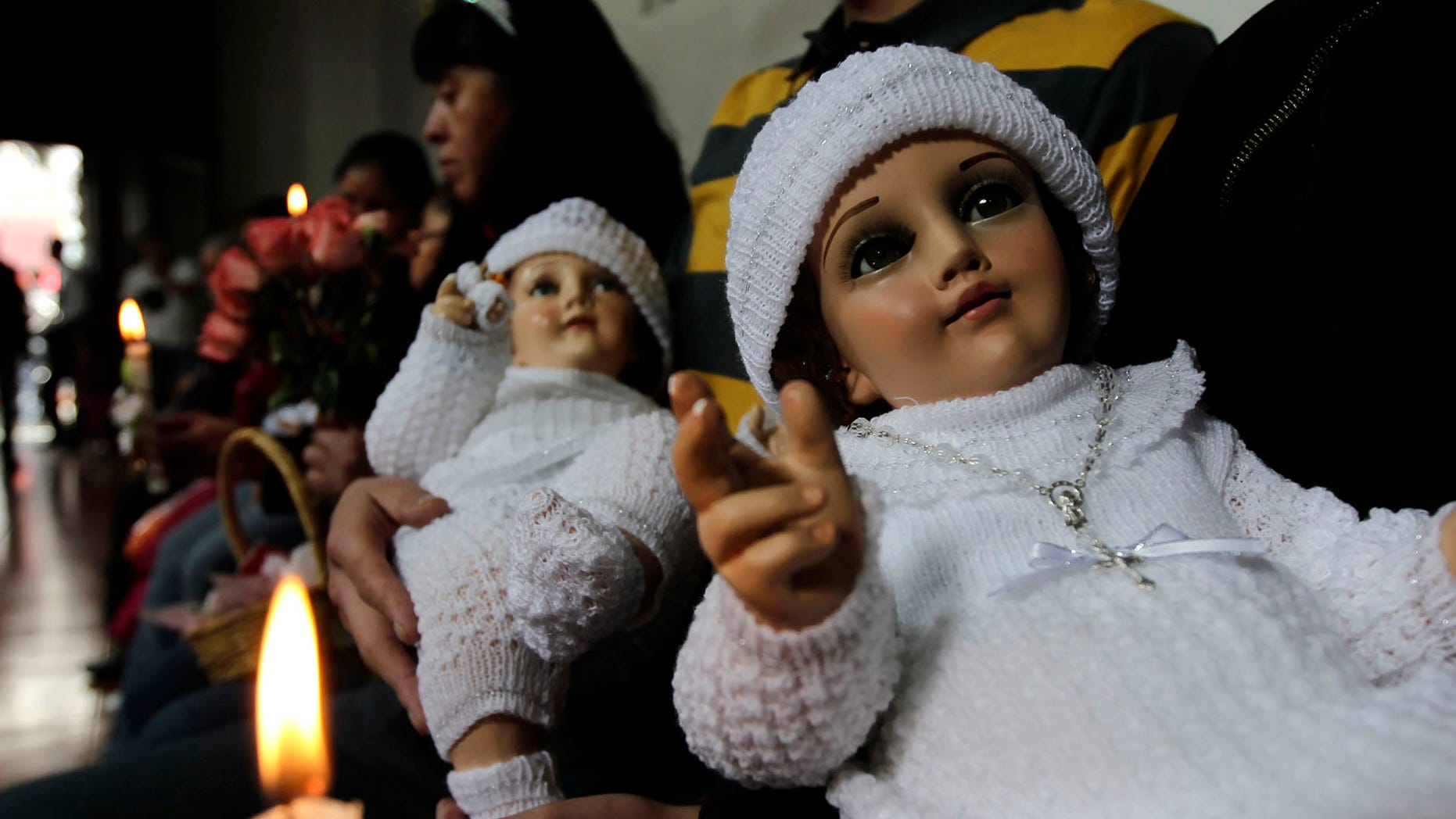 People hold dressed-up dolls representing baby Jesus during a mass in La Candelaria church in Mexico City.