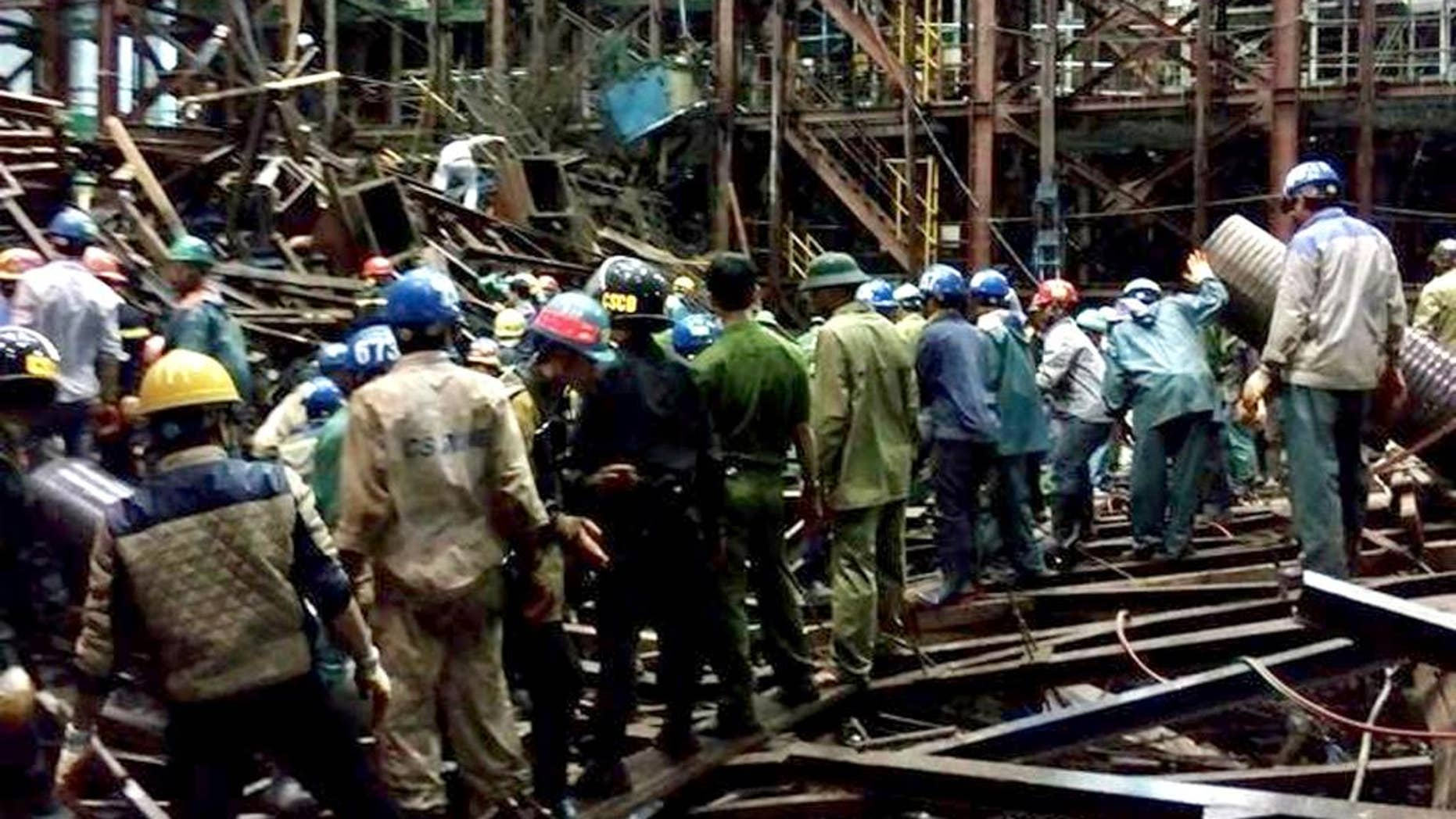 In this Wednesday March 25, 2015 photo, rescuers work through the rubble trying to find survivors after scaffolding collapsed in an economic zone in Ha Tinh province in central Vietnam. Police says at least 14 people were killed and 28 others were injured in the incident. (AP Photo/Vietnam News Agency, Cong Tuong)