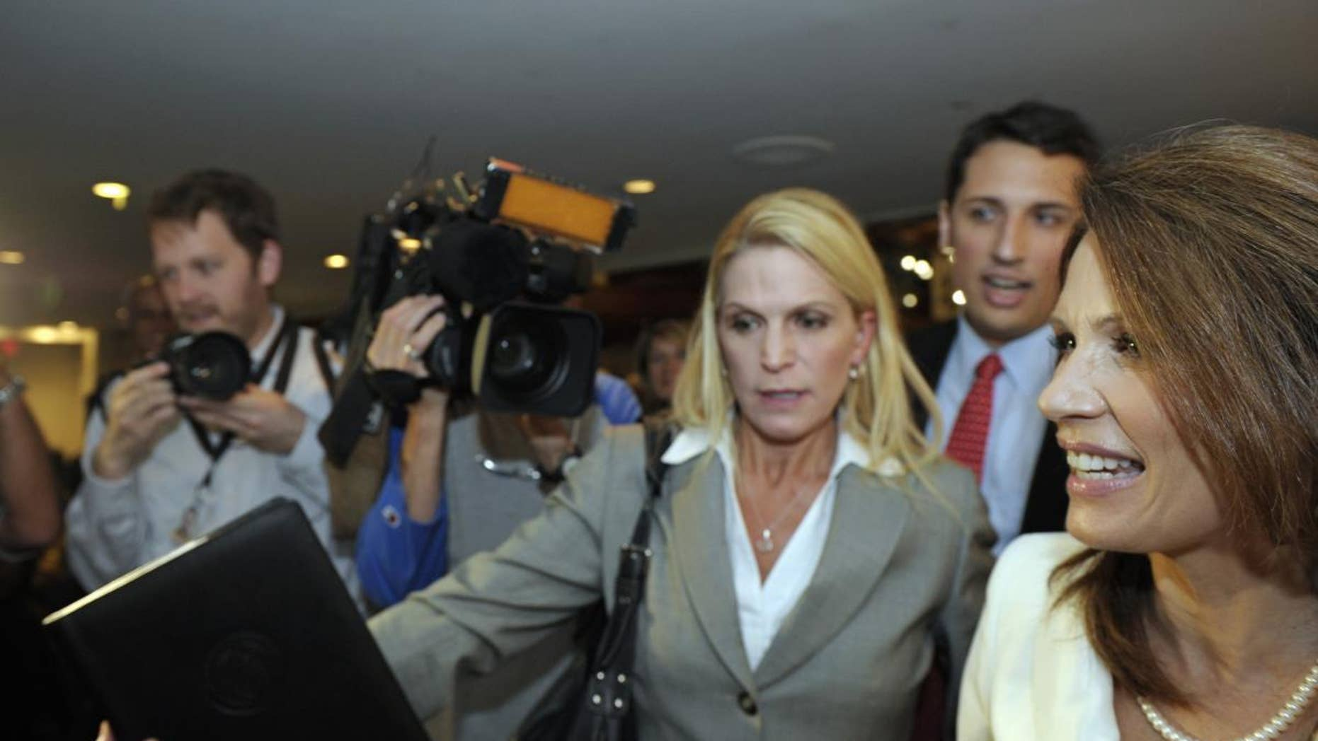 Republican presidential candidate, Rep. Michele Bachmann, R-Minn., right, is rushed past the news media as she departs a National Press Club luncheon in Washington, Thursday, July 28, 2011. . (AP Photo/Cliff Owen)