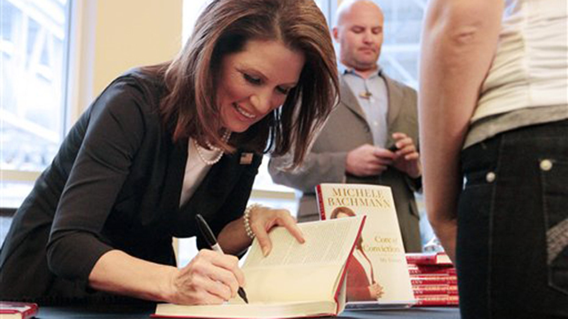 """Nov. 25, 2011: Rep. Michele Bachmann signs a copy of her new book, """"Core of Conviction,"""" during a campaign stop at the Mall of America in Bloomington, Minn."""