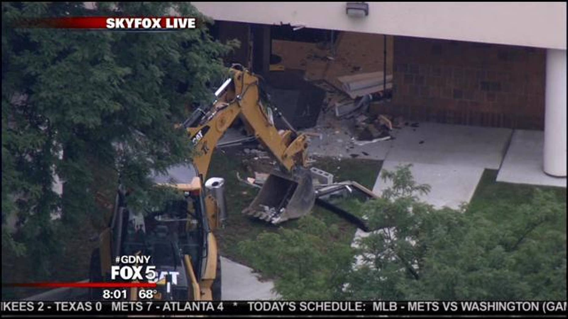 July 26, 2013: This photo shows the backhoe and damage left by a suspected thief at a Queens bank.