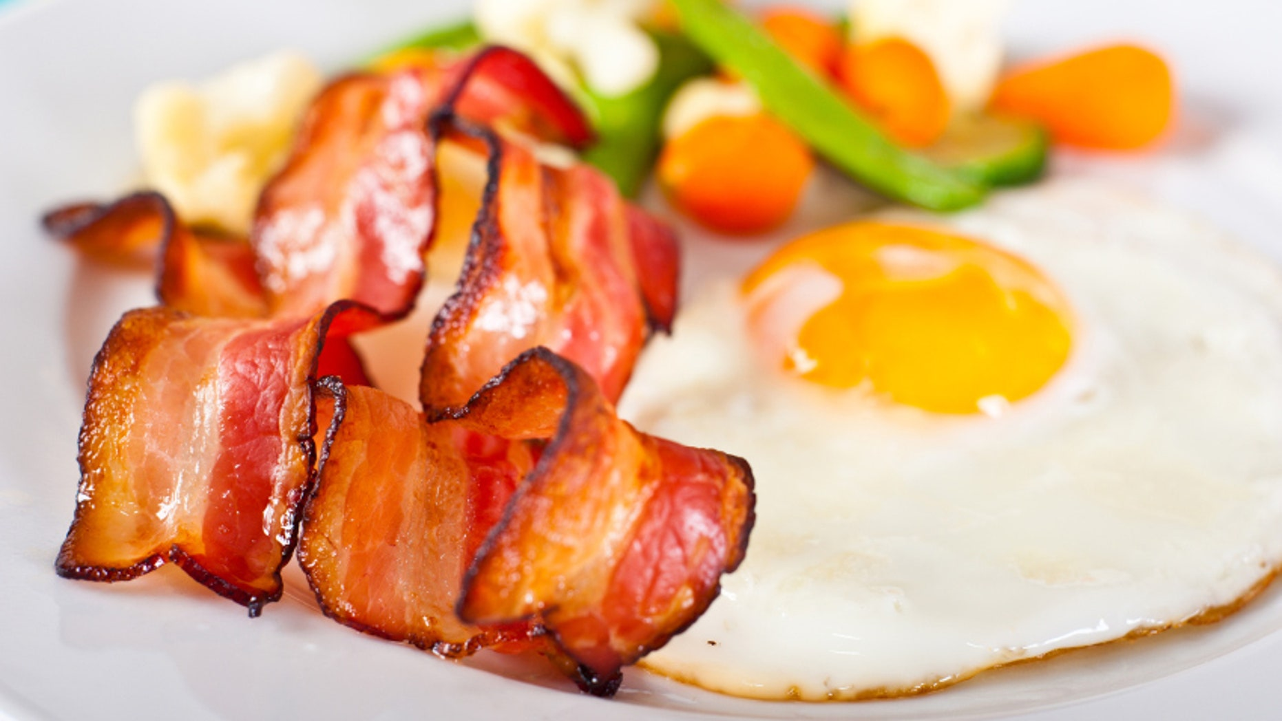 Close-up of fried egg with bacon and vegetables.