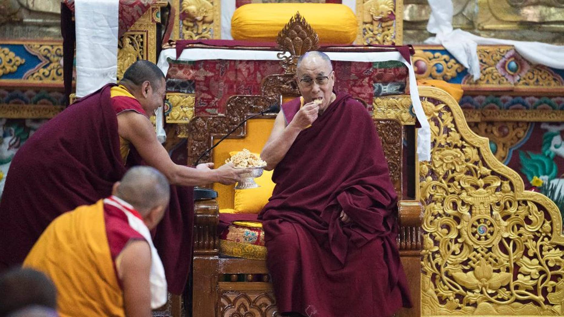 """Tibetan spiritual leader the Dalai Lama eats traditional Tibetan cookies upon arrival at the monastery in Tawang, in the northeastern Indian state of Arunachal Pradesh, Friday, April 7, 2017. The visit to Arunachal Pradesh, which China also claims as its territory, has raised tensions between the nuclear-armed Asian neighbors. China's Foreign Ministry has said the visit """"severely harms China's interests and the China-India relationship,"""" while India has cautioned Beijing to stay out of its internal affairs. (AP Photo/ Tenzin Choejor)"""