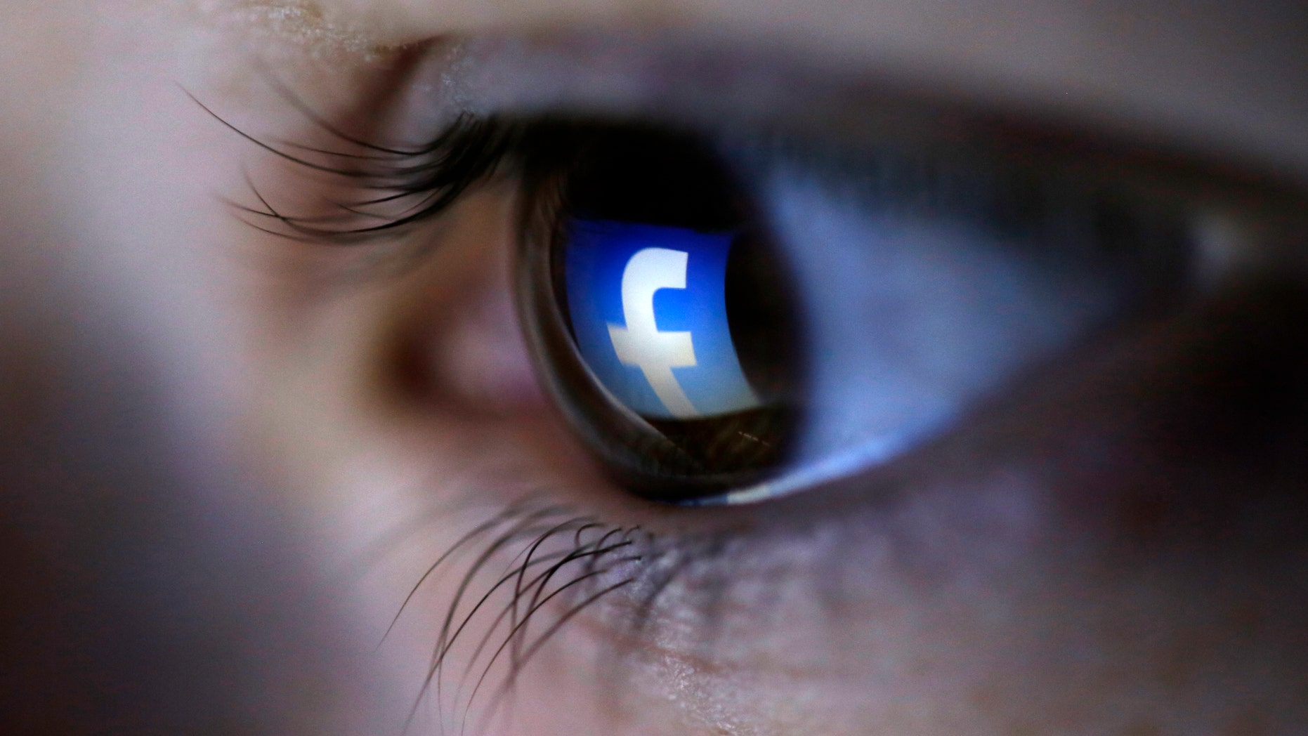 A picture illustration shows a Facebook logo reflected in a person's eye, in Zenica, March 13, 2015. (REUTERS/Dado Ruvic)