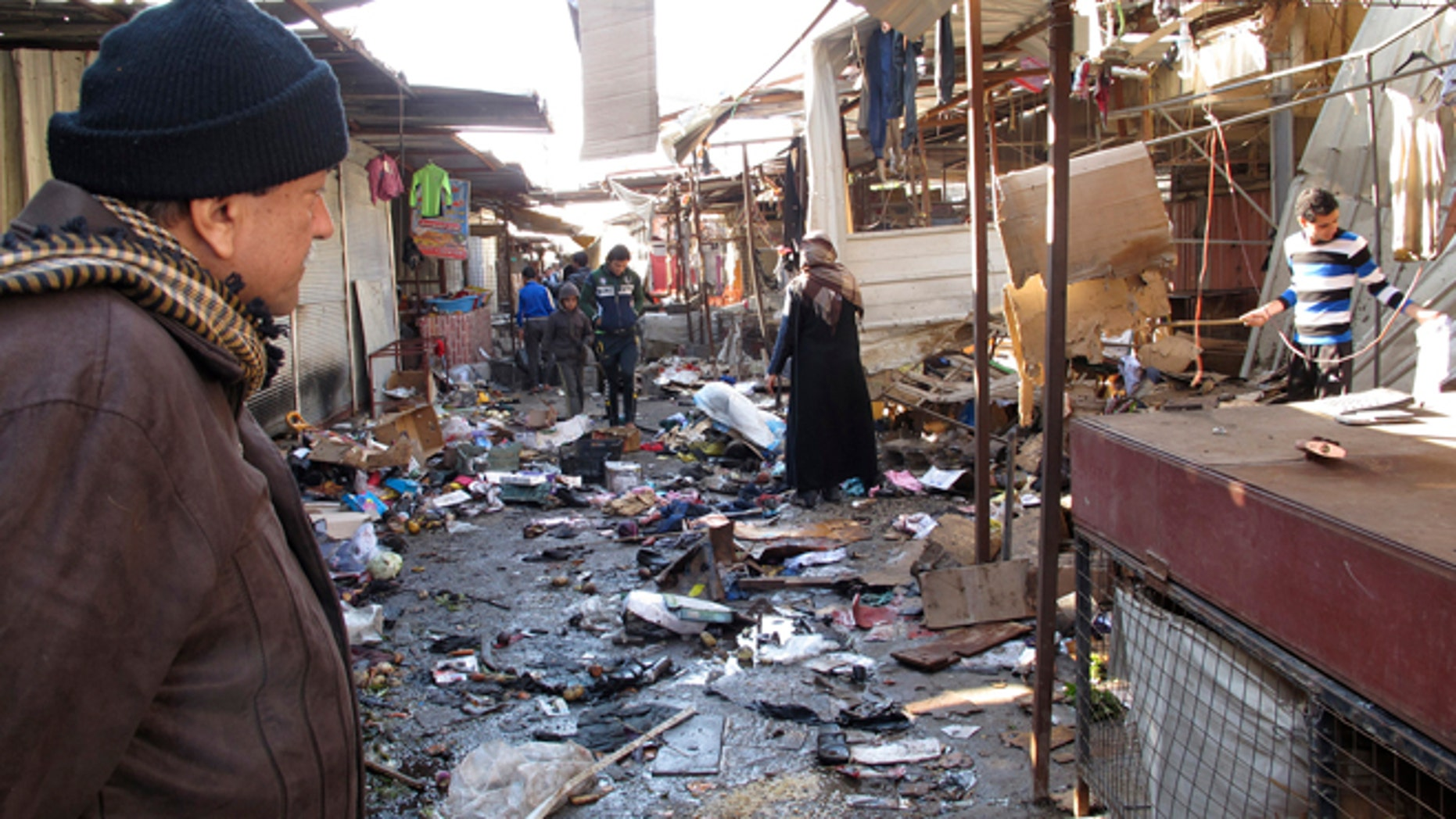 Dec. 25, 2013: A man looks at the site of bomb attack at a marketplace in Baghdad's Doura District.