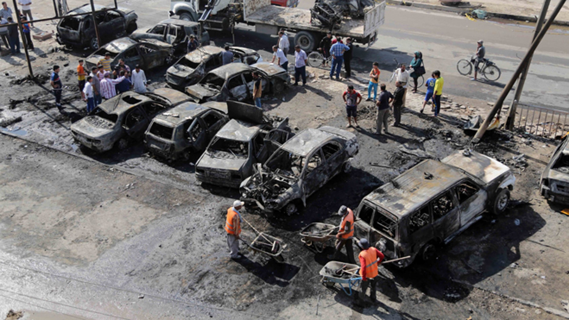 Oct. 27, 2013: Baghdad municipality workers clear debris while citizens inspect the site of a car bomb attack in a neighborhood of Baghdad, Iraq.