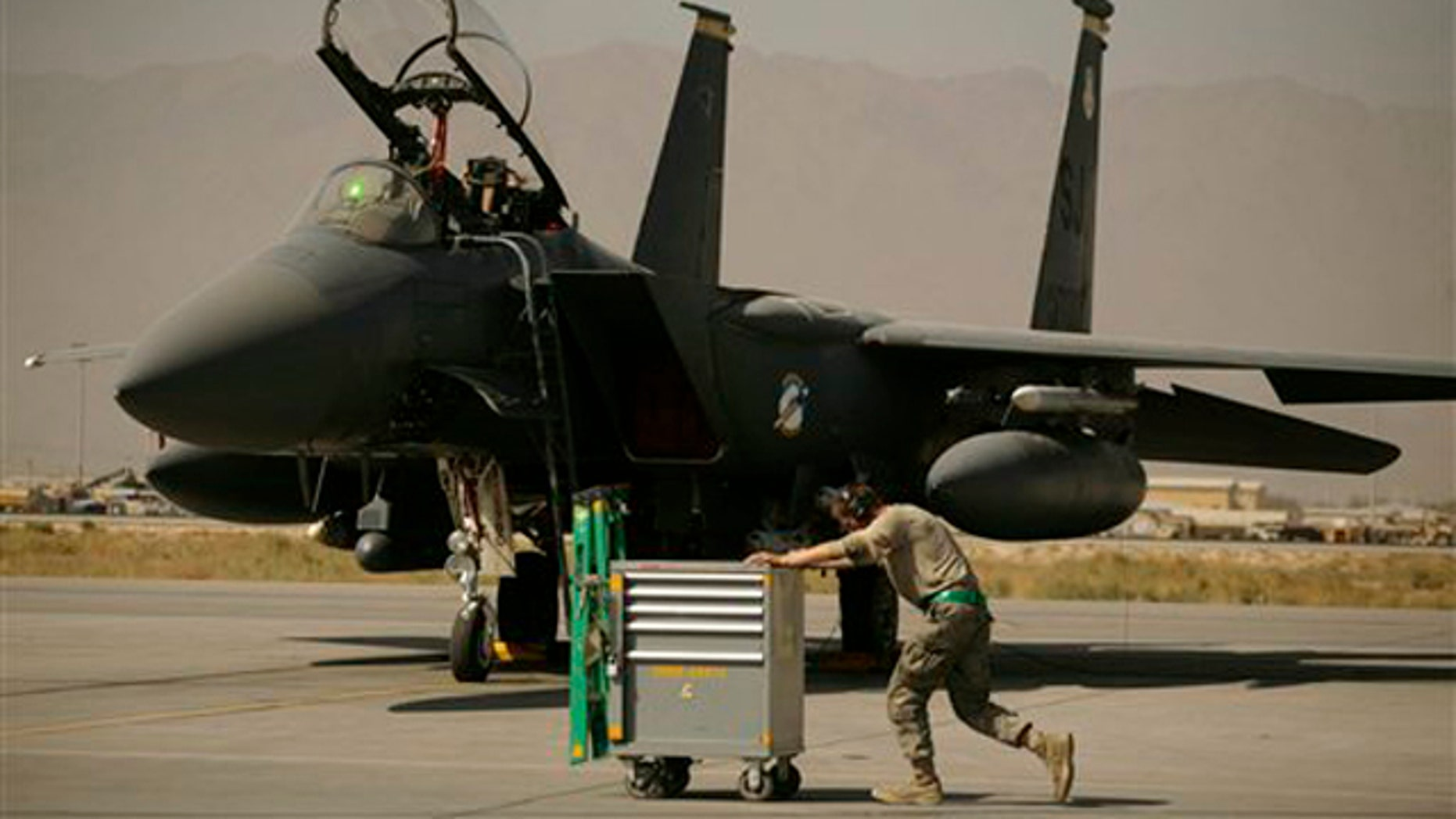 In this Oct. 17 picture, a U.S. Air Force airman passes an F-15E Strike Eagle at Bagram Air Field in Afghanistan. (AP Photo)