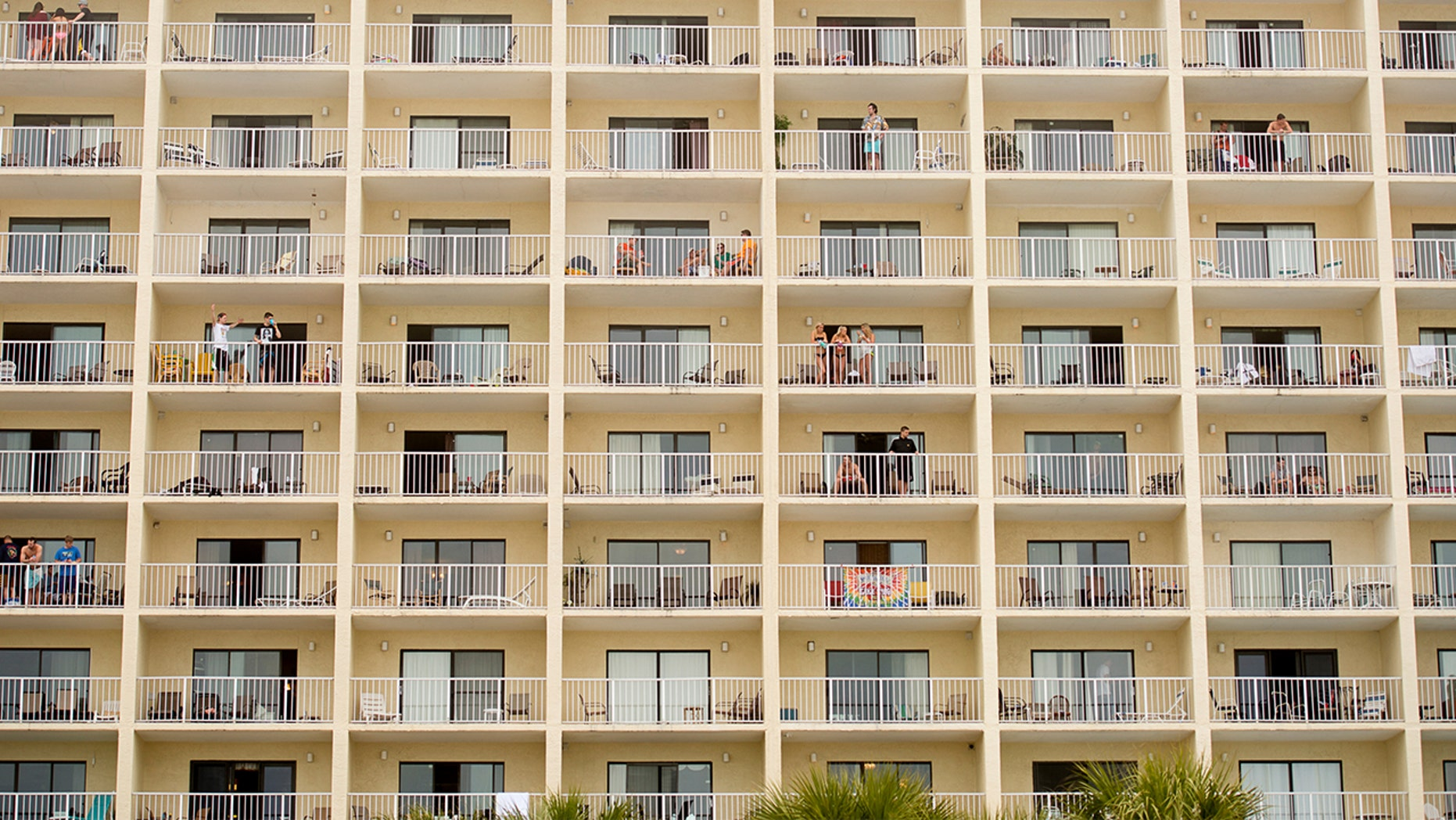 Partiers relax on hotel balconies during spring break festivities in Panama City Beach, Florida.