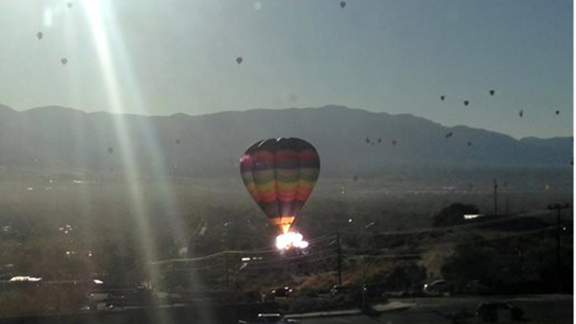 """Oct. 9, 2013: In this photo provided by the Catalyst, the balloon """"New Mexico Sunrise"""" strikes a power line after launching during mass ascension at the 2013 Albuquerque International Balloon Fiesta in Albuquerque, N.M."""