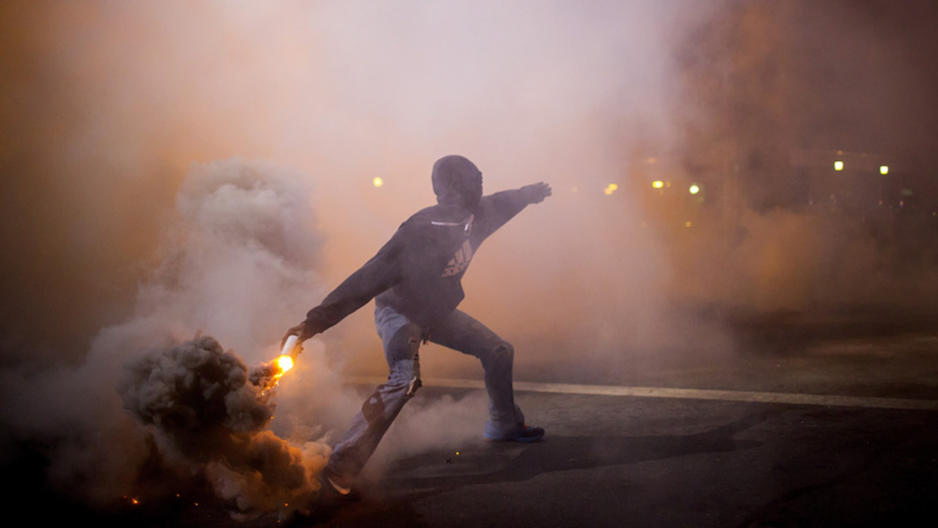 A protester throws a gas canister back at police during clashes at North Ave and Pennsylvania Ave in Baltimore, Maryland April 28, 2015. Baltimore erupted in violence on Monday as hundreds of rioters looted stores, burned buildings and at least 15 police officers were injured following the funeral of Freddie Gray, a 25-year-old black man who died after suffering a spinal injury in police custody. The riots broke out blocks from where the funeral of Gray took place and spread through much of west Baltimore. REUTERS/Eric Thayer - GF10000076849