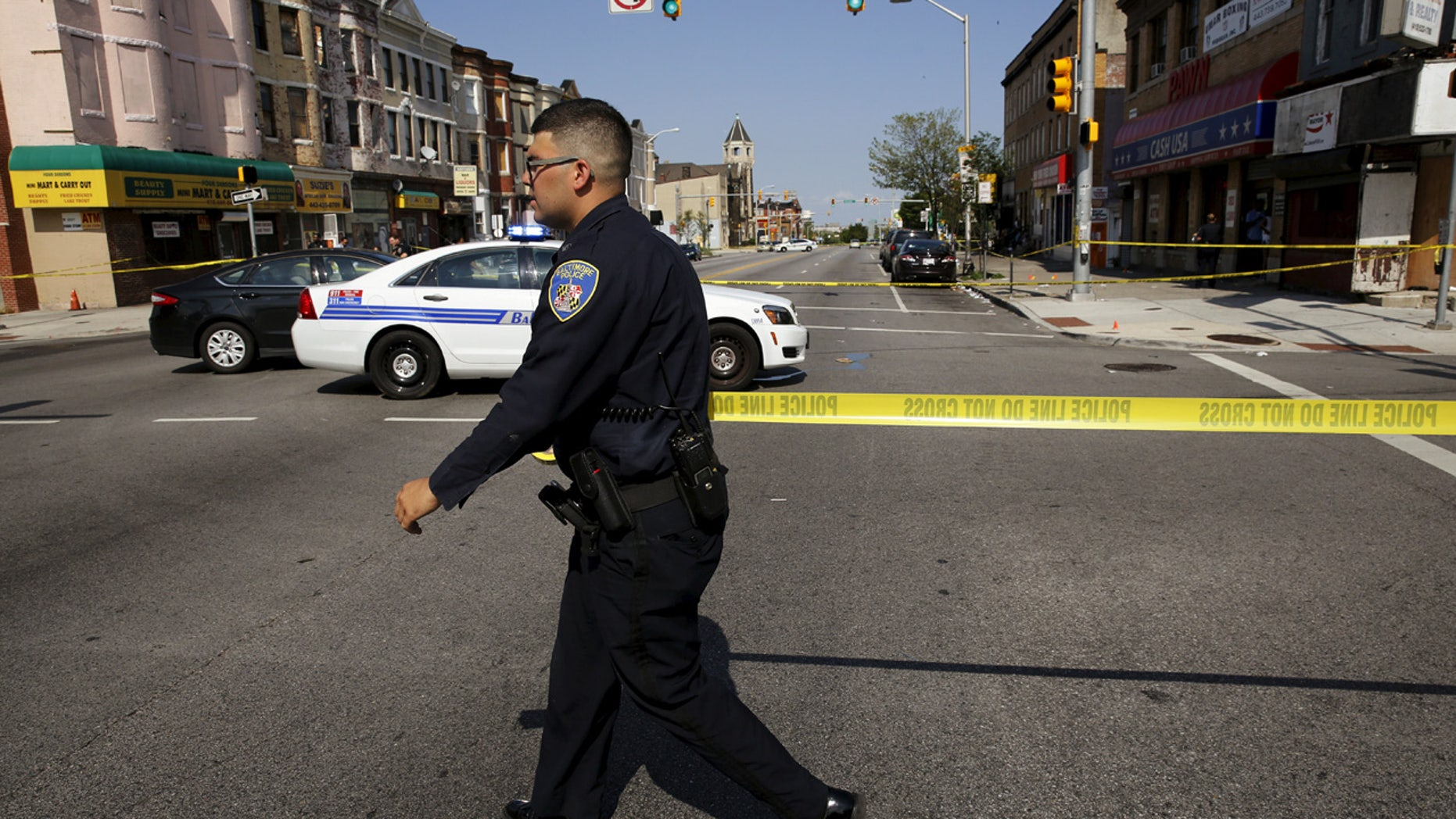 A Baltimore police officer attempts to secure a crime scene with tape at the scene of a shooting at the intersection of West North Avenue and Druid Hill Avenue in West Baltimore, Maryland.