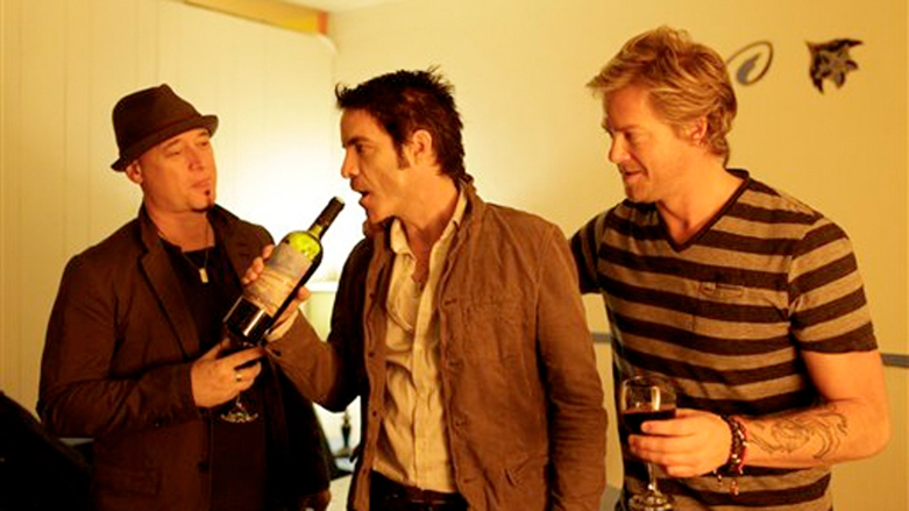 April 11, 2012: From left, Jimmy Stafford, Patrick Monahan, and Scott Underwood of the band Train sample some of their wine.