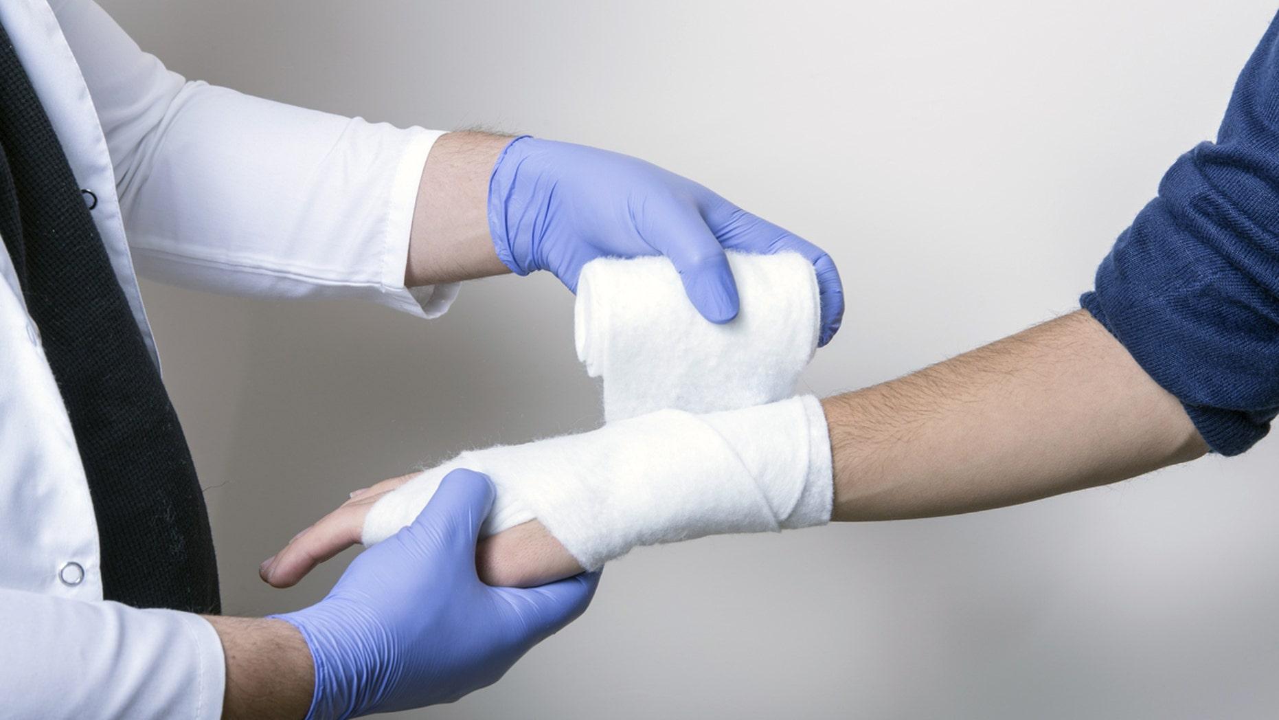 Pediatrician wraps wrist of an unidentified student.