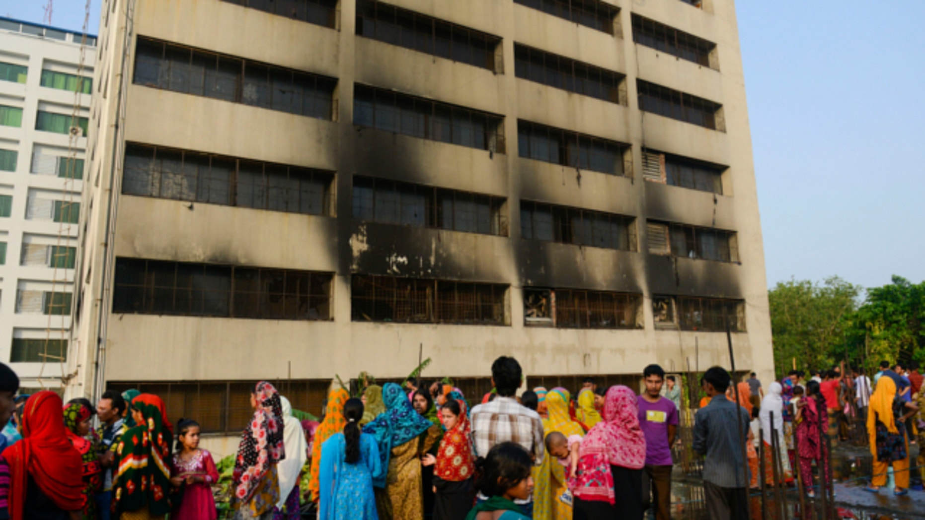May 9, 2013: Workers stand outside an 11-story building that houses the Tung Hai Sweater Ltd. factory and apartments after a fire in Dhaka, Bangladesh.
