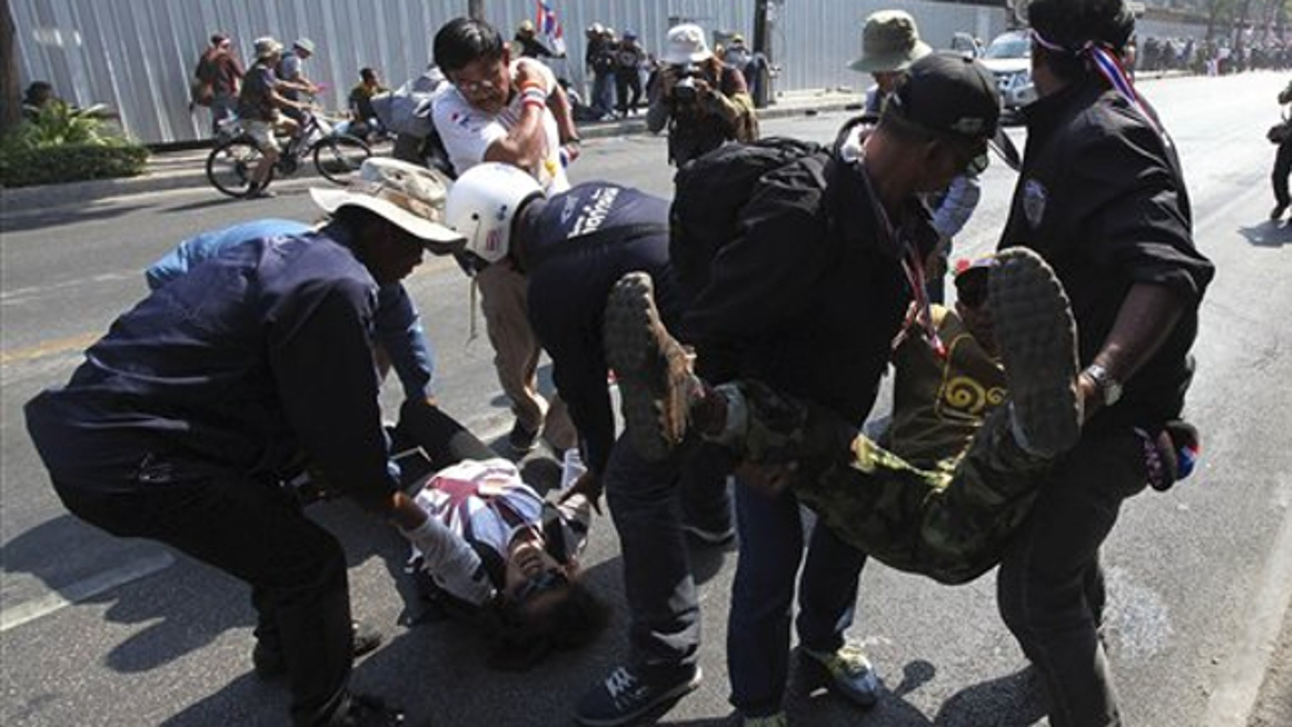 Jan. 17, 2014: Injured anti-government protesters are taken out from a street by other protesters during a demonstration in Bangkok, Thailand.