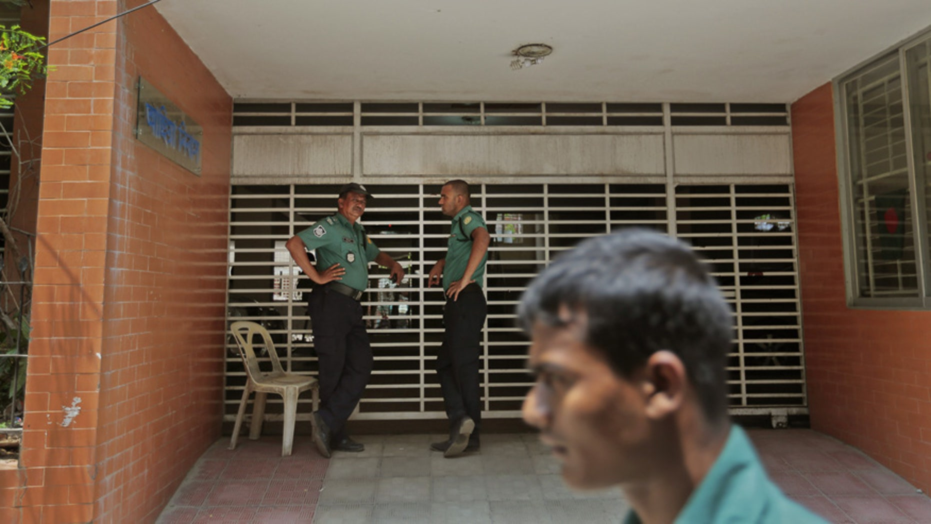 April 26, 2016: Bangladeshi policemen stand guard at the entrance to the building where two people were stabbed to death by unidentified assailants in Dhaka, Bangladesh.