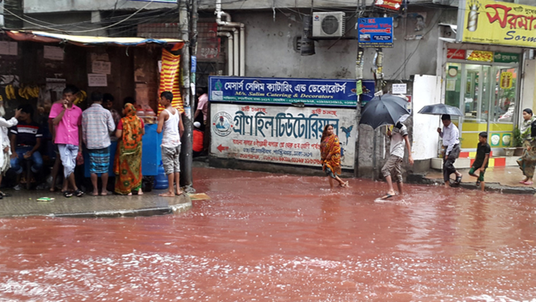 In this Tuesday, Sept. 13, 2016 photo, people wade past a road turned red after blood from sacrificial animals on Eid al-Adha mixed with water from heavy rainfall in Dhaka, Bangladesh.