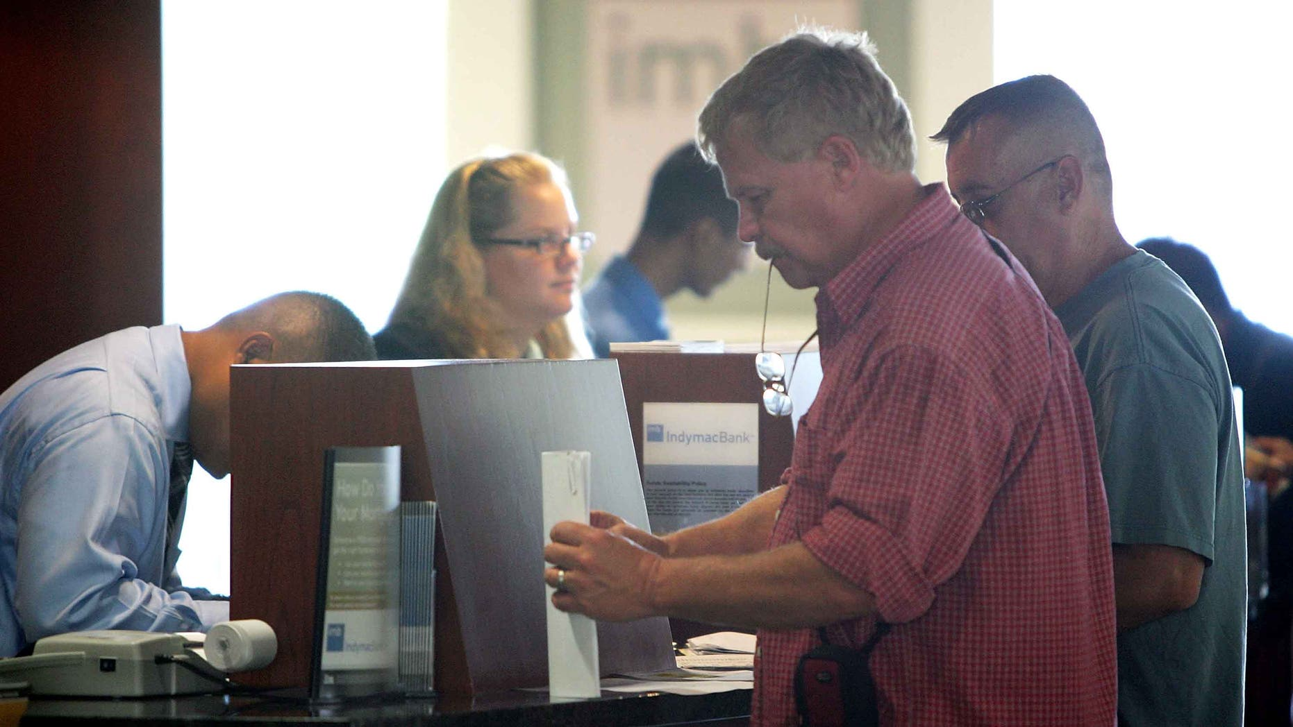 PASADENA, CA - JULY 14:  Customers (R) carry out their transactions with tellers after waiting in line with hundreds of other nervous customers to get into an IndyMac Bank, open for the first time since the July 11 federal government takeover of the thrift, on July 14, 2008 in Pasadena, California. IndyMac, which was already in trouble because of it's subprime mortgages with people with bad or no credit history, was shut down three hours early on a Friday and remained closed over the weekend after customers withdrew $1.9 billion. Regulators say it is the second-largest bank failure ever in the US. As all 33 IndyMac branches reopen, customers with home-equity credit lines will reportedly find their accounts frozen while transactions involving deposit accounts will be conducted as normal under the name, IndyMac Federal Bank. Over the weekend, the Federal Reserve also worked on shoring up lenders Fannie Mae and Freddie Mac which control almost half of the national mortgage debt and are in danger of collapse as well.  (Photo by David McNew/Getty Images)
