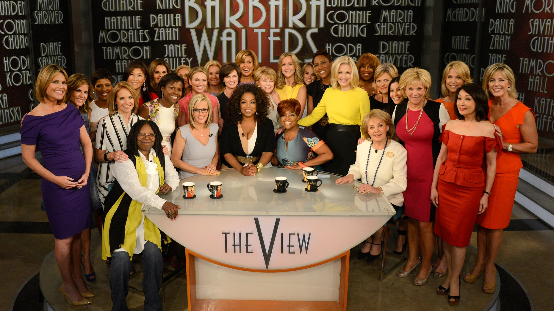 """May 15, 2014. Seated from left, Whoopi Goldberg, Jenny McCarthy, Oprah Winfrey, Sherri Shepherd and Barbara Walters posing with female broadcasters during a taping of Walters' final co-host appearance on """"The View,"""" in New York."""
