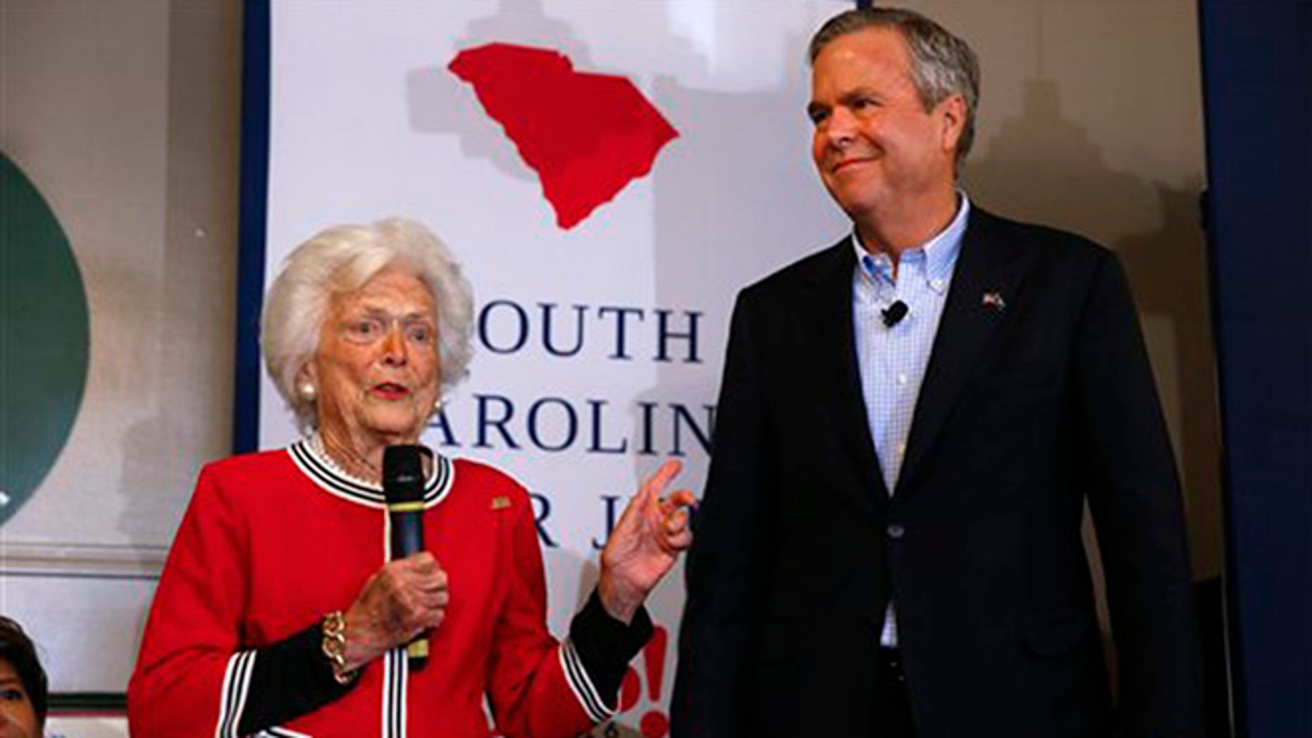 Republican presidential candidate, former Florida Gov. Jeb Bush, listens as his mother, former first lady Barbara speak during a campaign stop at Wade's Restaurant, Friday, Feb. 19, 2016 in Spartanburg, S.C. (AP Photo/Paul Sancya)