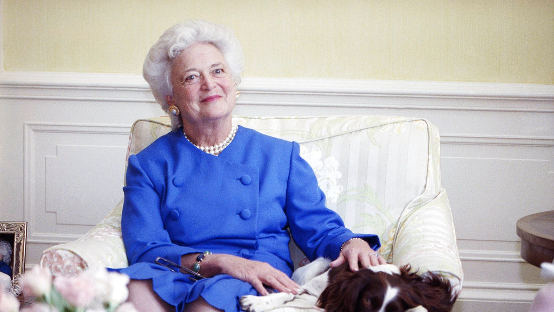 FILE - In this 1990 file photo, first lady Barbara Bush poses with her dog Millie in Washington. A family spokesman said Tuesday, April 17, 2018, that former first lady Barbara Bush has died at the age of 92. (AP Photo/Doug Mills, File)