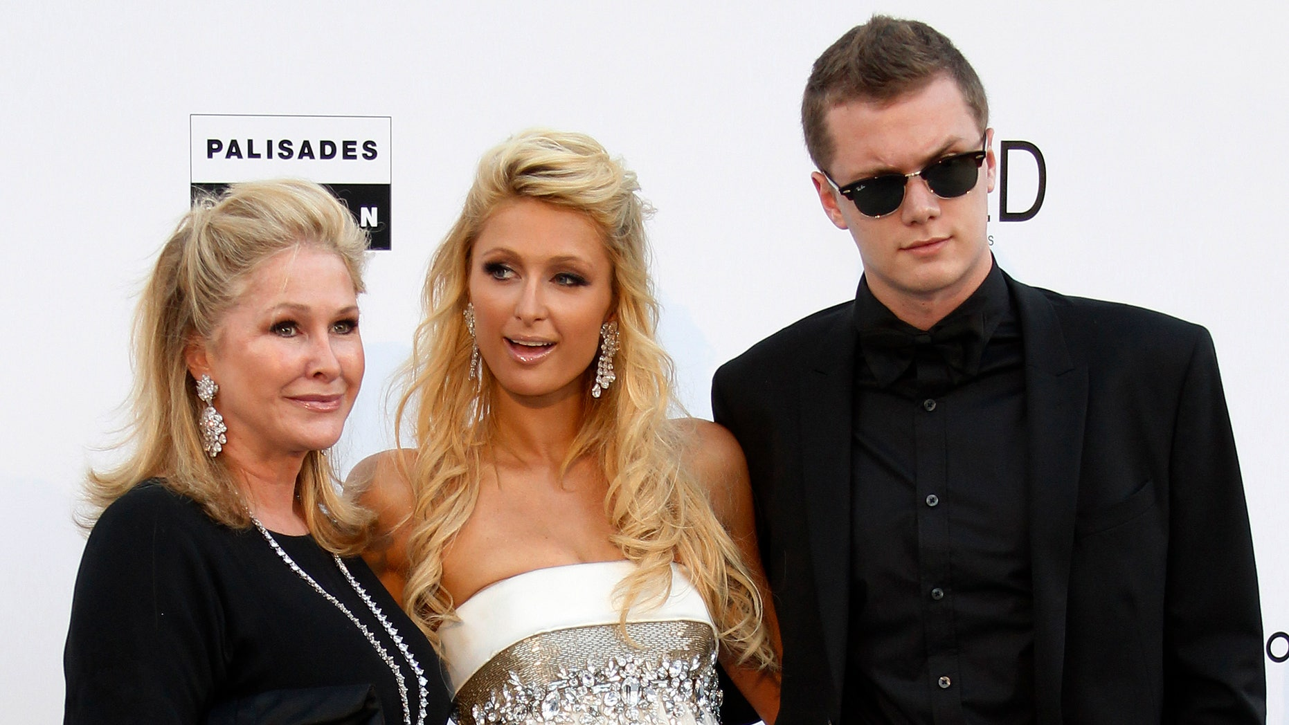 May 20, 2010. Paris Hilton (C), her mother Kathy (L) and her brother Barron Nicholas Hilton arrive for the amfAR's Cinema Against AIDS 2010 event in Antibes during the 63rd Cannes Film Festival.
