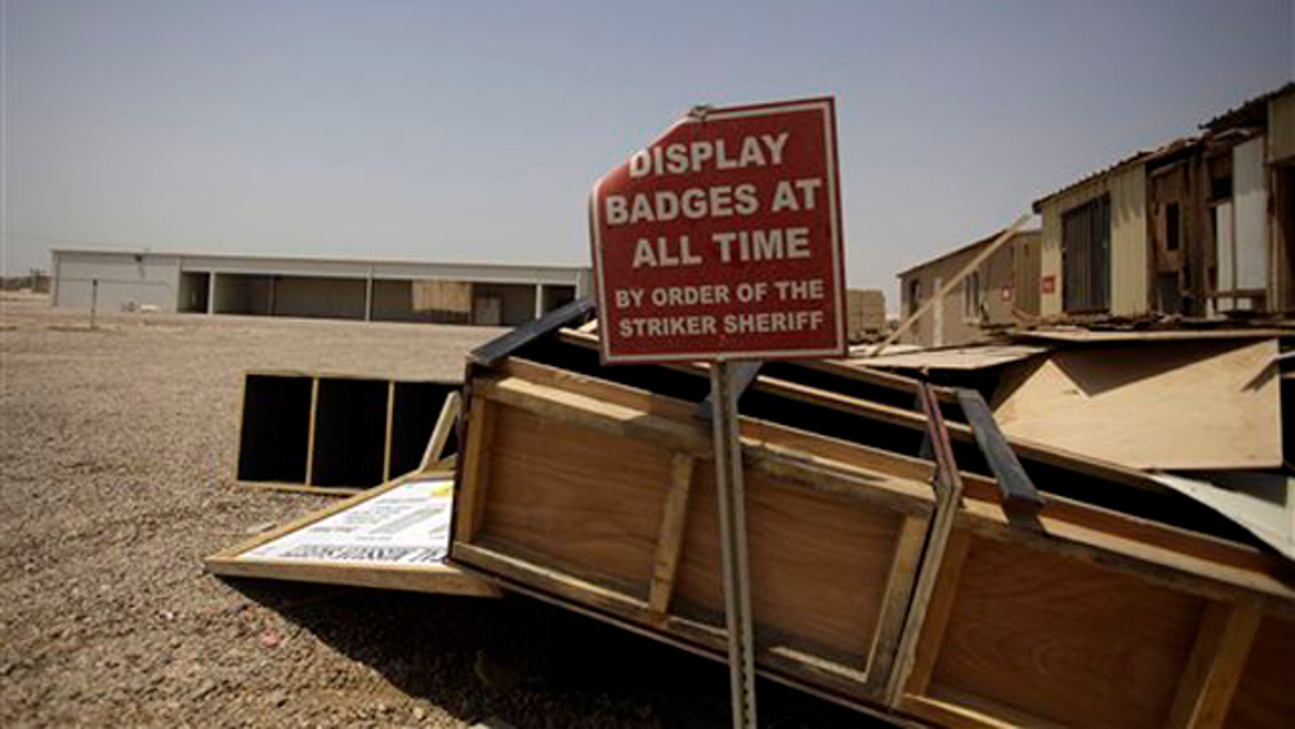 In this Aug. 4 photo, scraps of wood from the post office and a sign remain at a shuttered Camp Sather, part of the sprawling U.S. military Victory Base Complex that is set to close in Baghdad, Iraq.