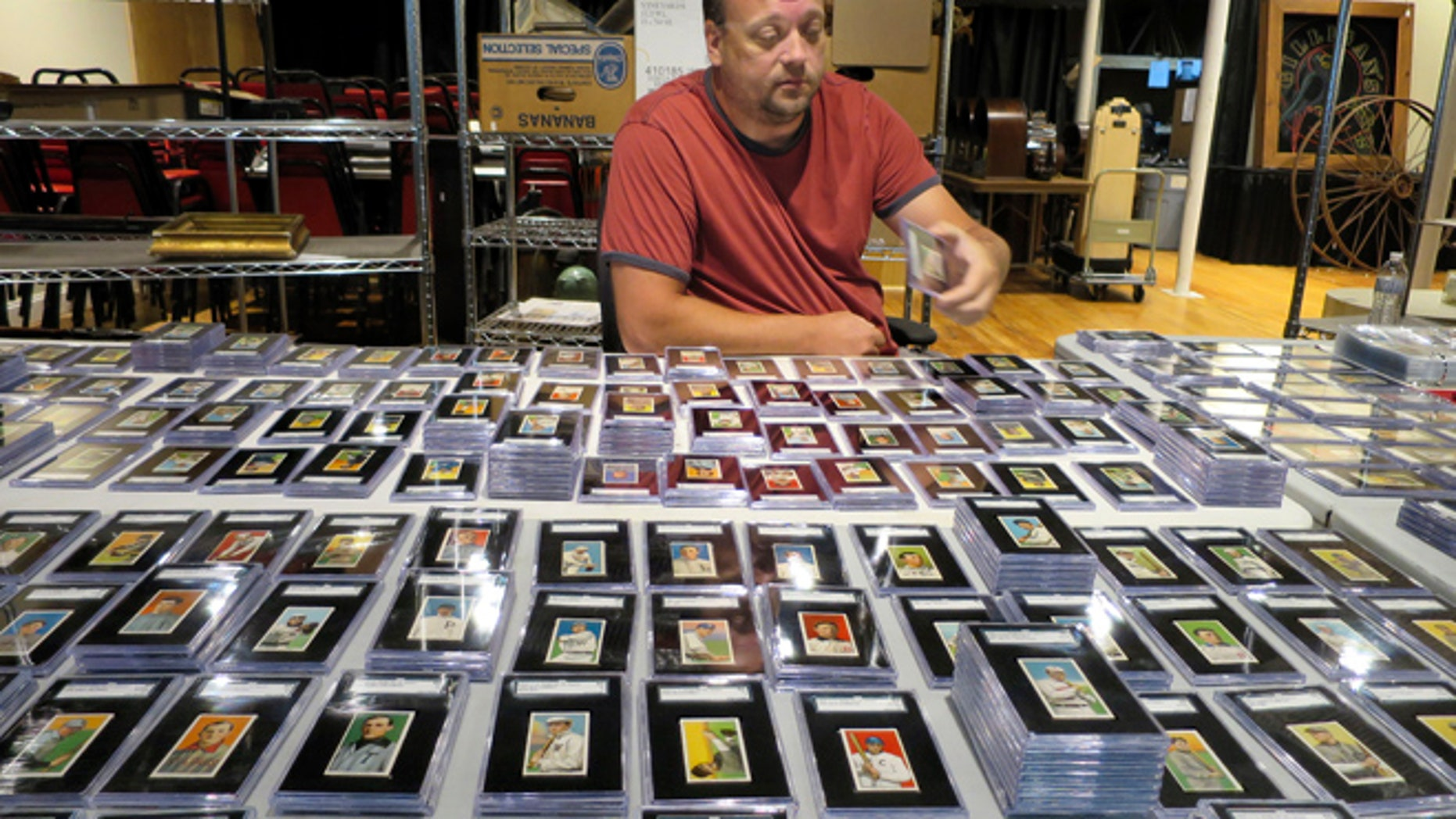 In this Aug. 25, 2014 photo, Troy Thibodeau, from Saco River Auction Co., examines a collection of more than 1,400 baseball cards from 1909, 1910, and 1911 in Biddeford, Maine. The collection will be auctioned off starting in January 2015. (AP/David Sharp)