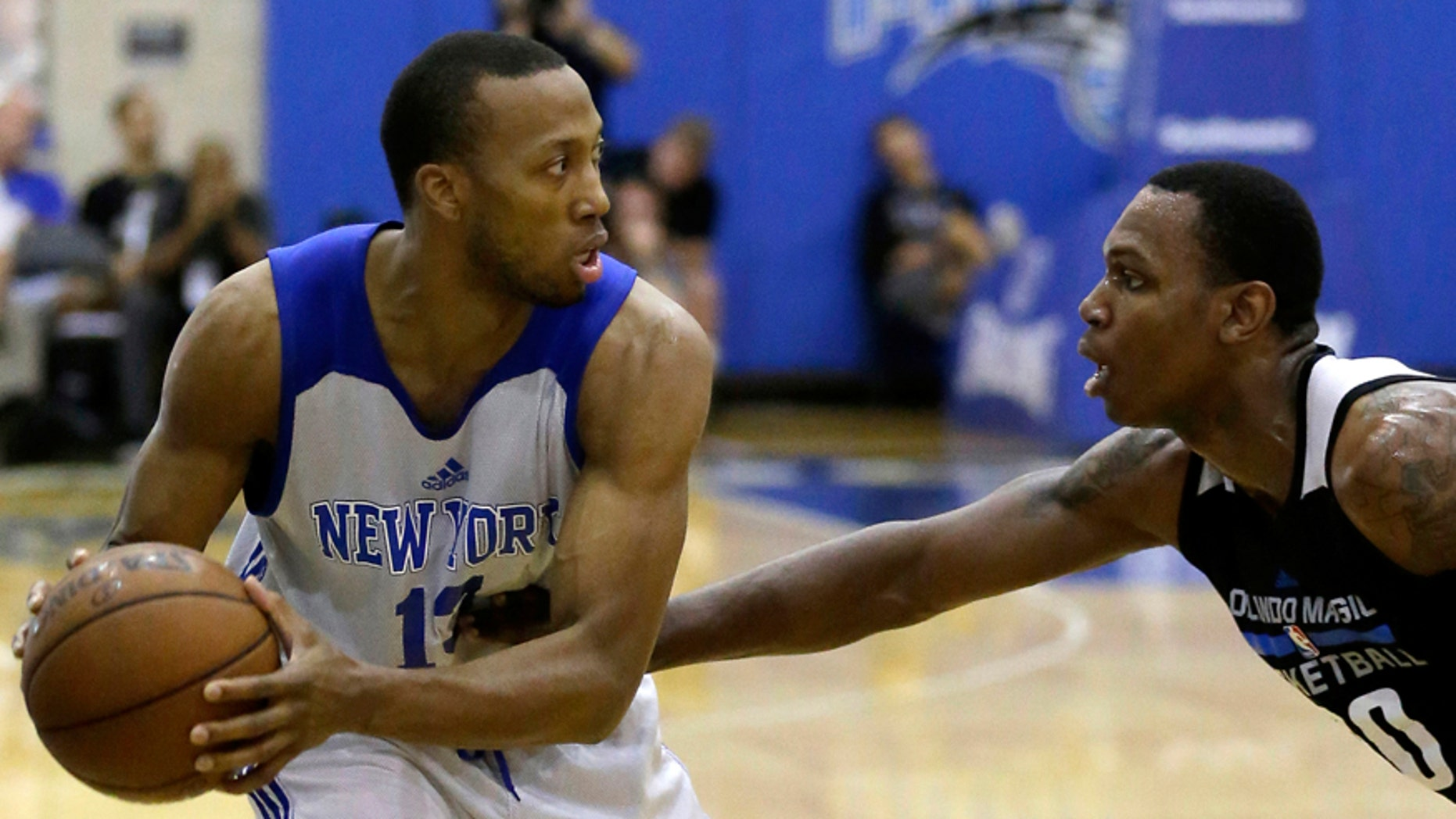 FILE - This is a Wednesday, July 6, 2016  file photo of New York Knicks' Akil Mitchell, left, as he looks to pass the ball around Orlando Magic White's Treveon Graham during the first half of an NBA summer league basketball game in Orlando, Fla. American basketball player Akil Mitchell's eye popped out of its socket after he was poked in the face while going for a rebound during a game in New Zealand  Thursday Jan. 26, 2017 .(AP Photo/John Raoux, File)