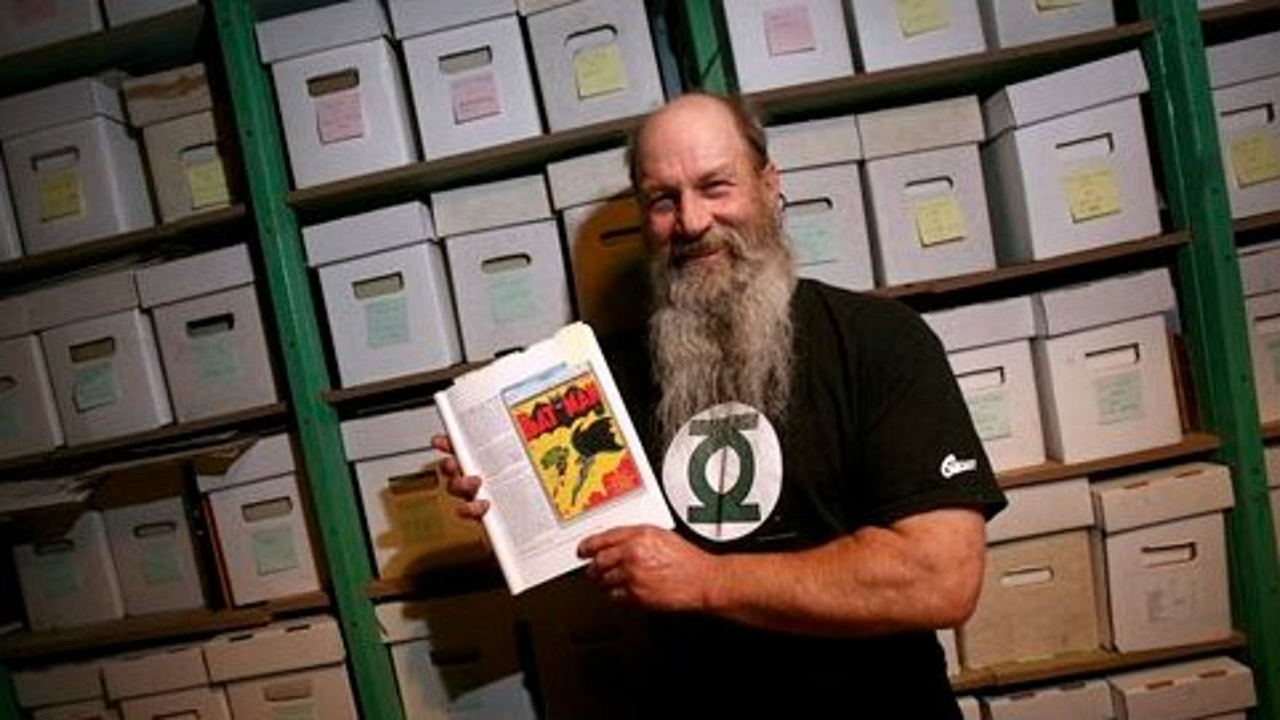 July 29: Comic book collector Mike Wheat poses with a book showing the cover of Batman No. 1 in front of boxes containing tens of thousands of comic books at his Fairbanks, Alaska home. Wheat put his copy of the 1940 Batman No. 1 on the auction block through Dallas-based Heritage Auction Galleries. (AP)
